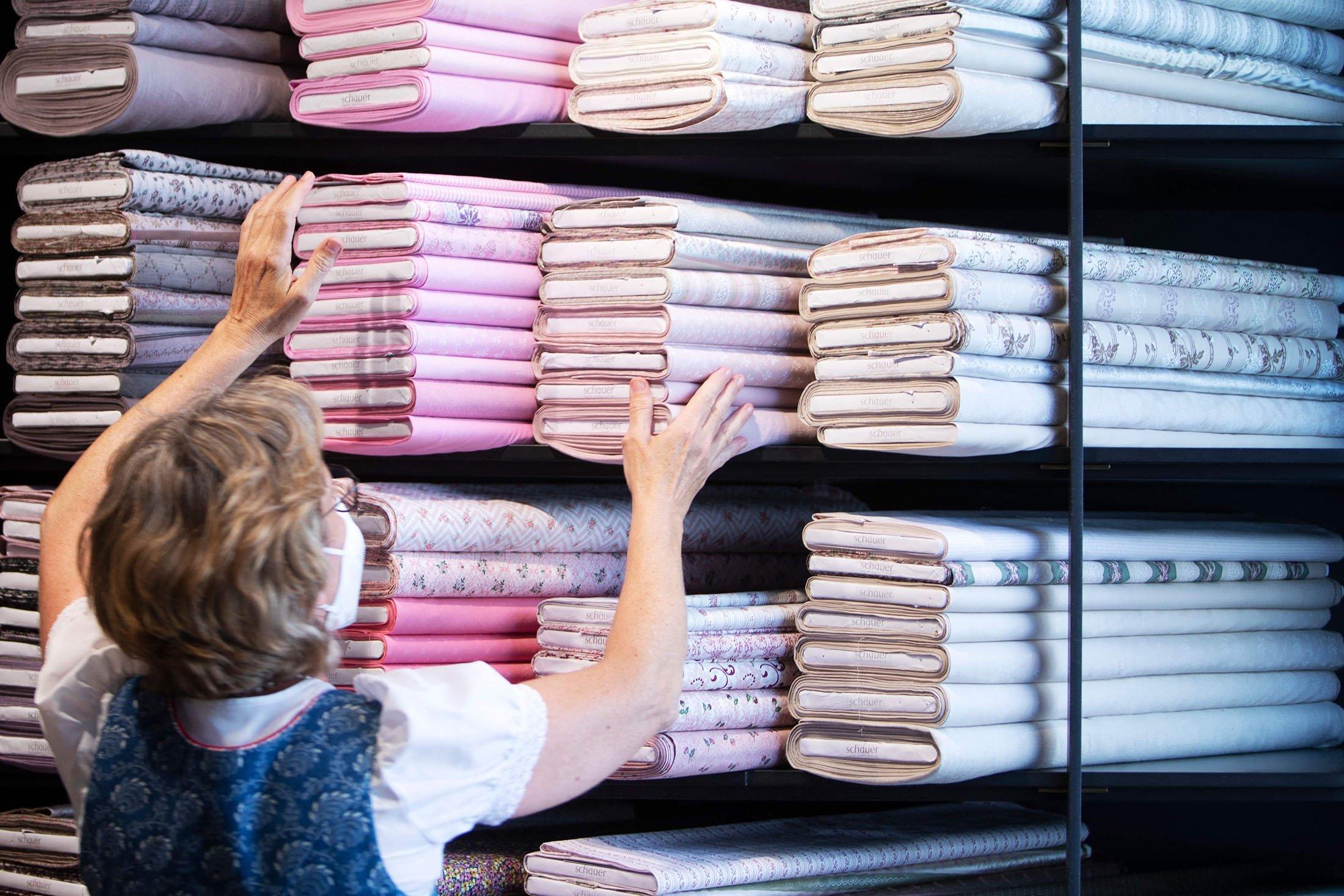 An employee arranges the fabrics at the Schauer Atelier dirndl shop in Bad Ischl, Upper Austria, June 24, 2021. (AFP Photo)