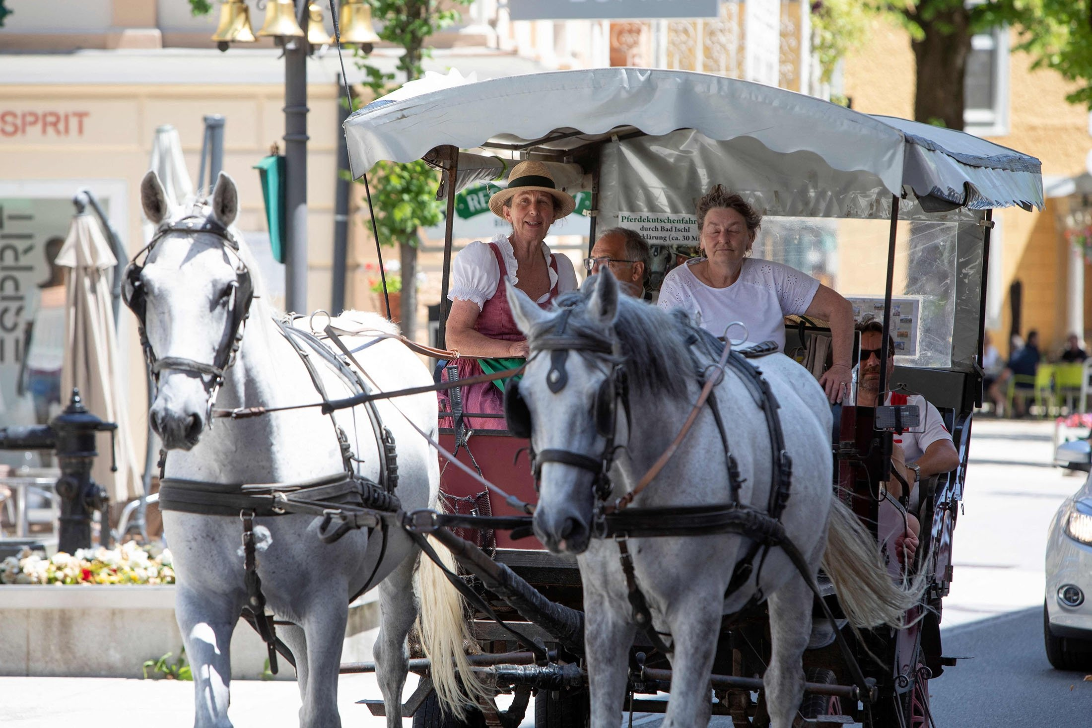 A woman in a traditional dirndl dress sits on a horse carriage in Bad Ischl, Upper Austria, June 24, 2021. (AFP Photo)