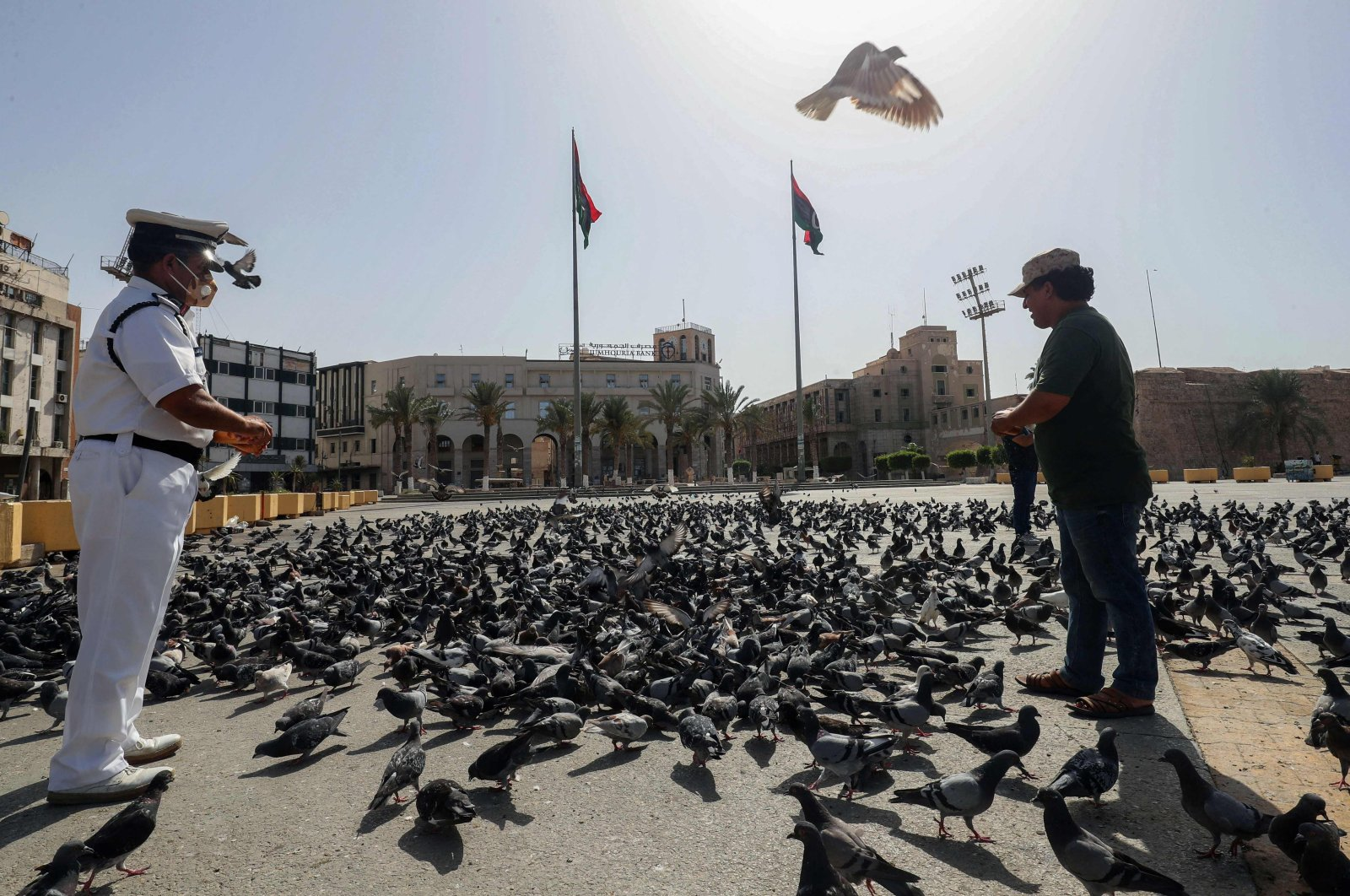 Libyan men feed pigeons in an empty Martyrs square in downtown Tripoli, Libya, Aug, 7, 2021. (AFP Photo)