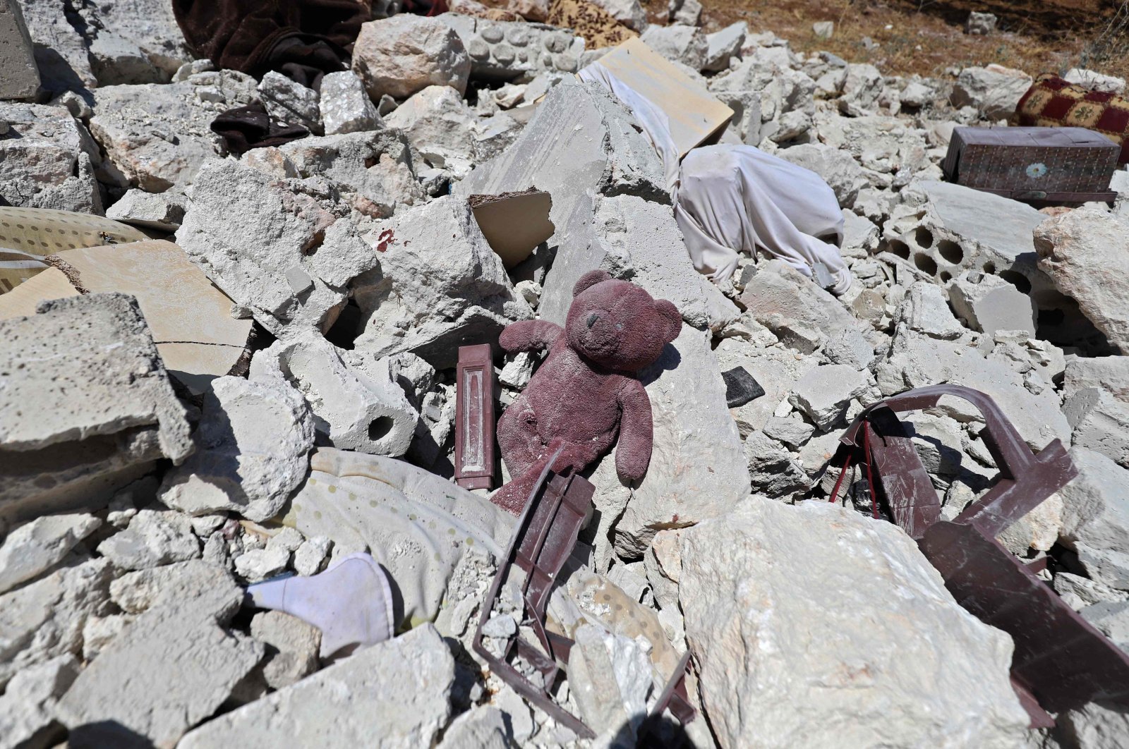A child's teddy bear is pictured amidst the rubble of a house, following reported shelling by regime forces, in the village of Serja, in the southern part of Syria's Idlib province, on July 17, 2021. (Photo by Abdulaziz KETAZ / AFP)