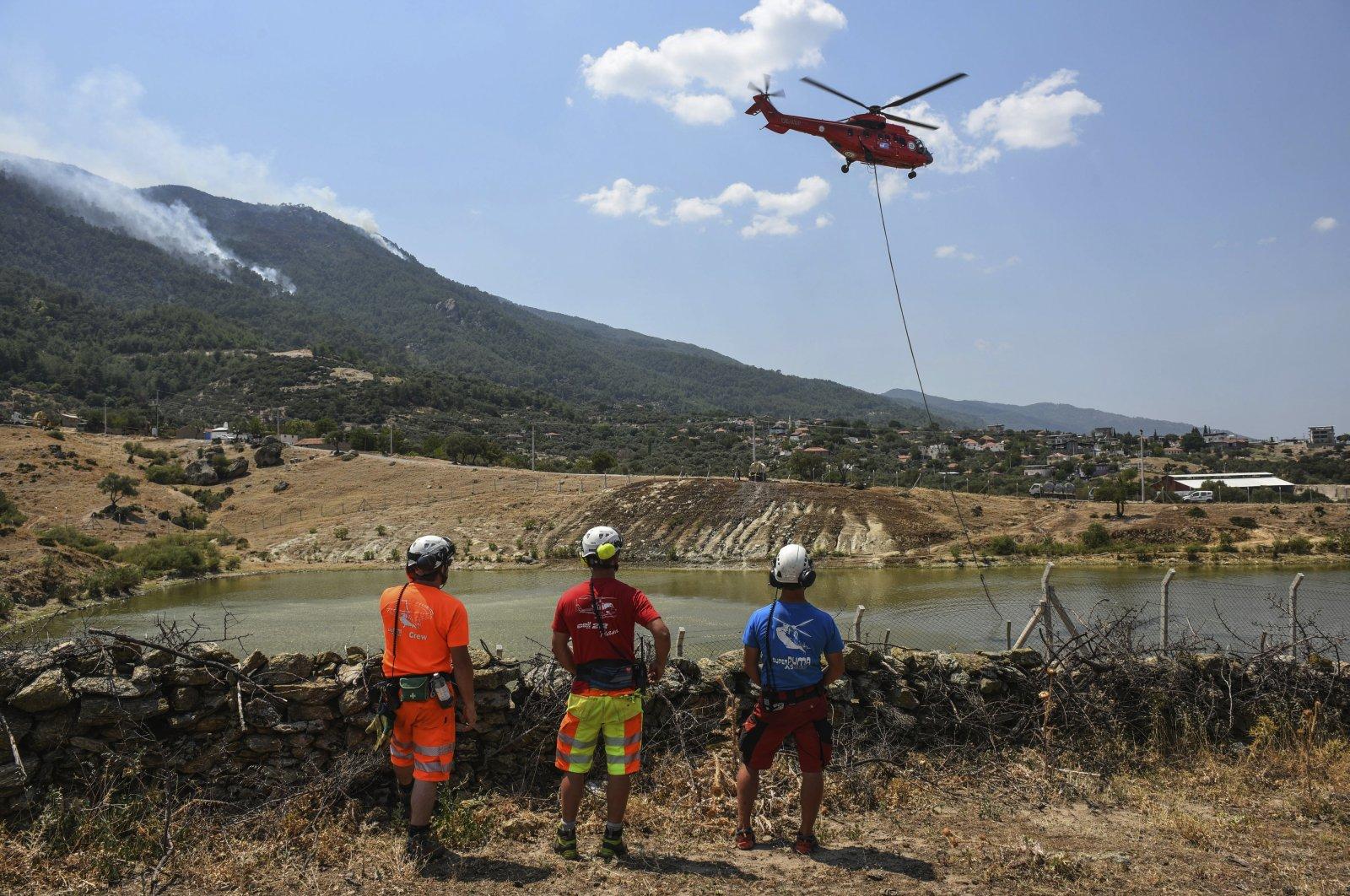 A firefighting helicopter takes water from a lake in Akçaova Village, near Çine, Aydın, northwestern Turkey, Aug. 7, 2021. (AP Photo)