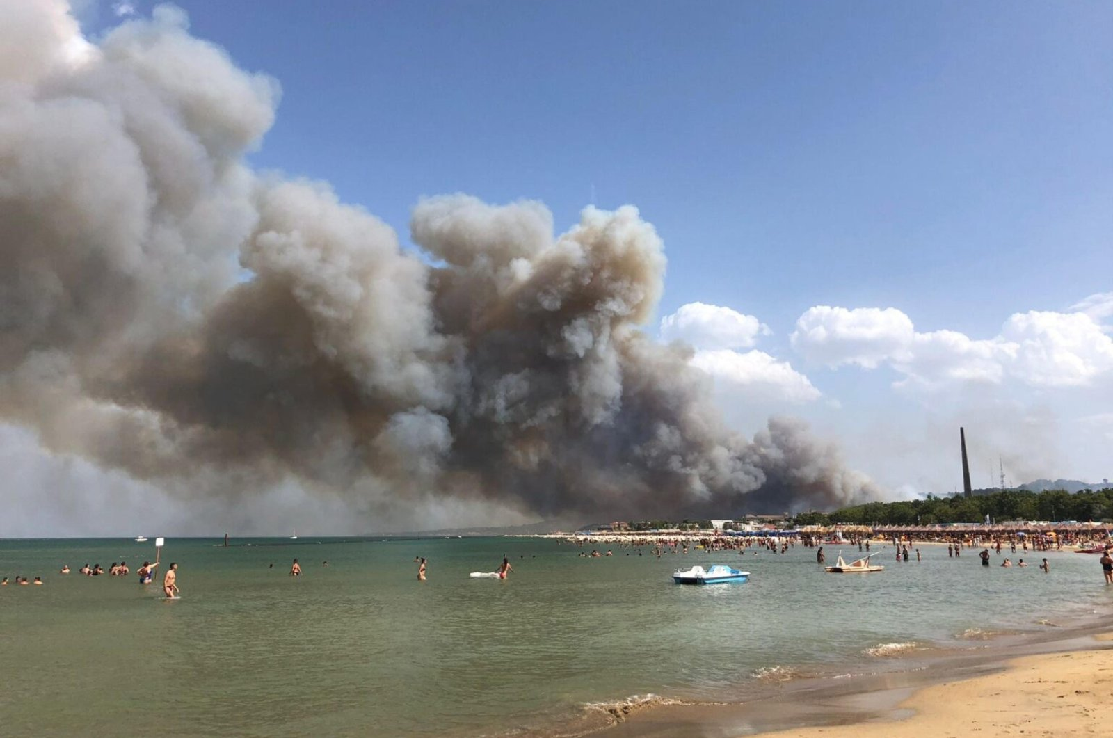 Smoke billows from fire in the Dannunziana Reserve as people watch from the waters at Pescara, Italy, Aug. 1, 2021. (EPA Photo)