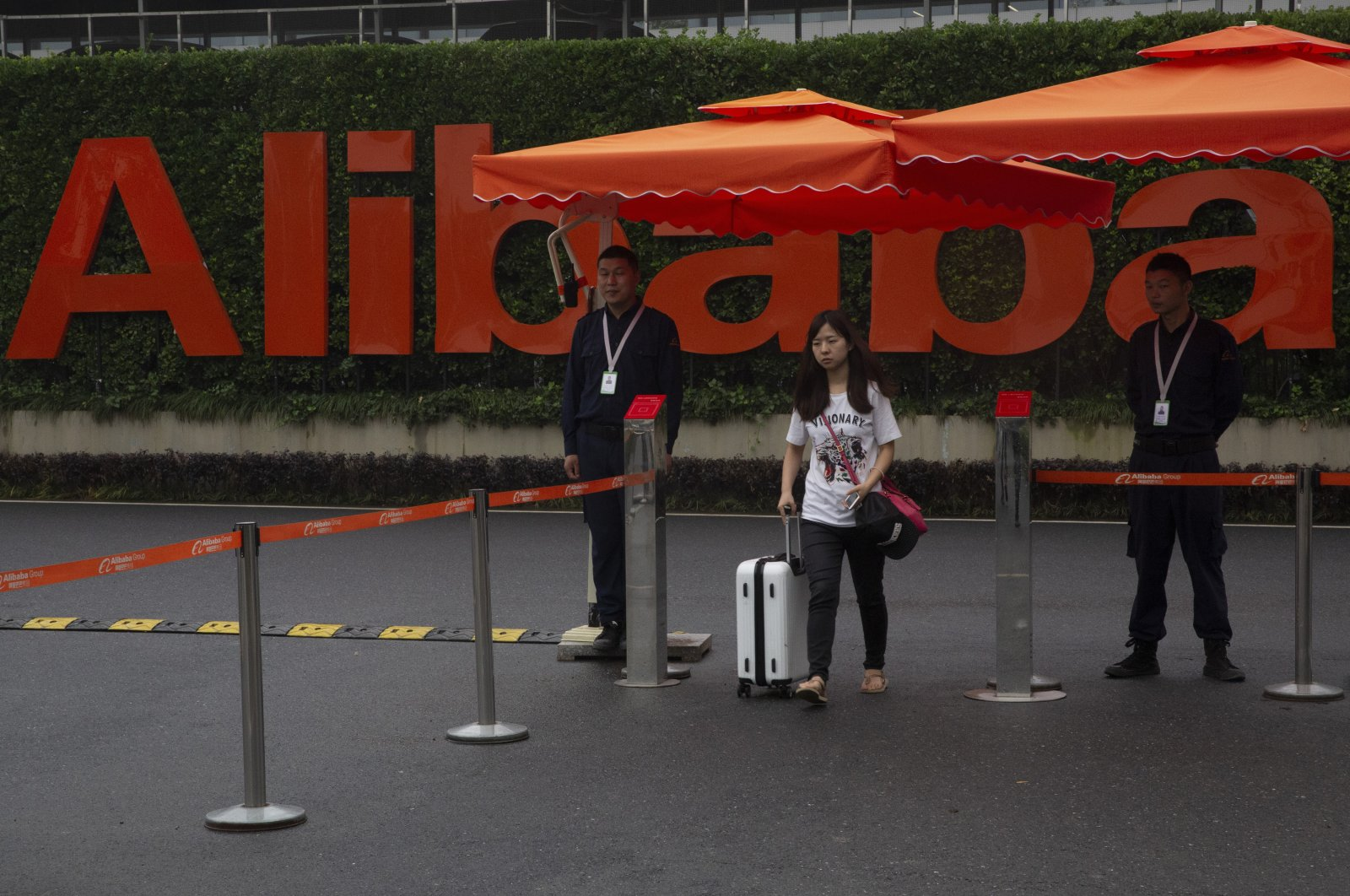 A woman pushing a trolley bag passes by security guards at the entrance to the Alibaba Group headquarters in Hangzhou, in Zhejiang province, eastern China, May 27, 2016. (AP Photo)