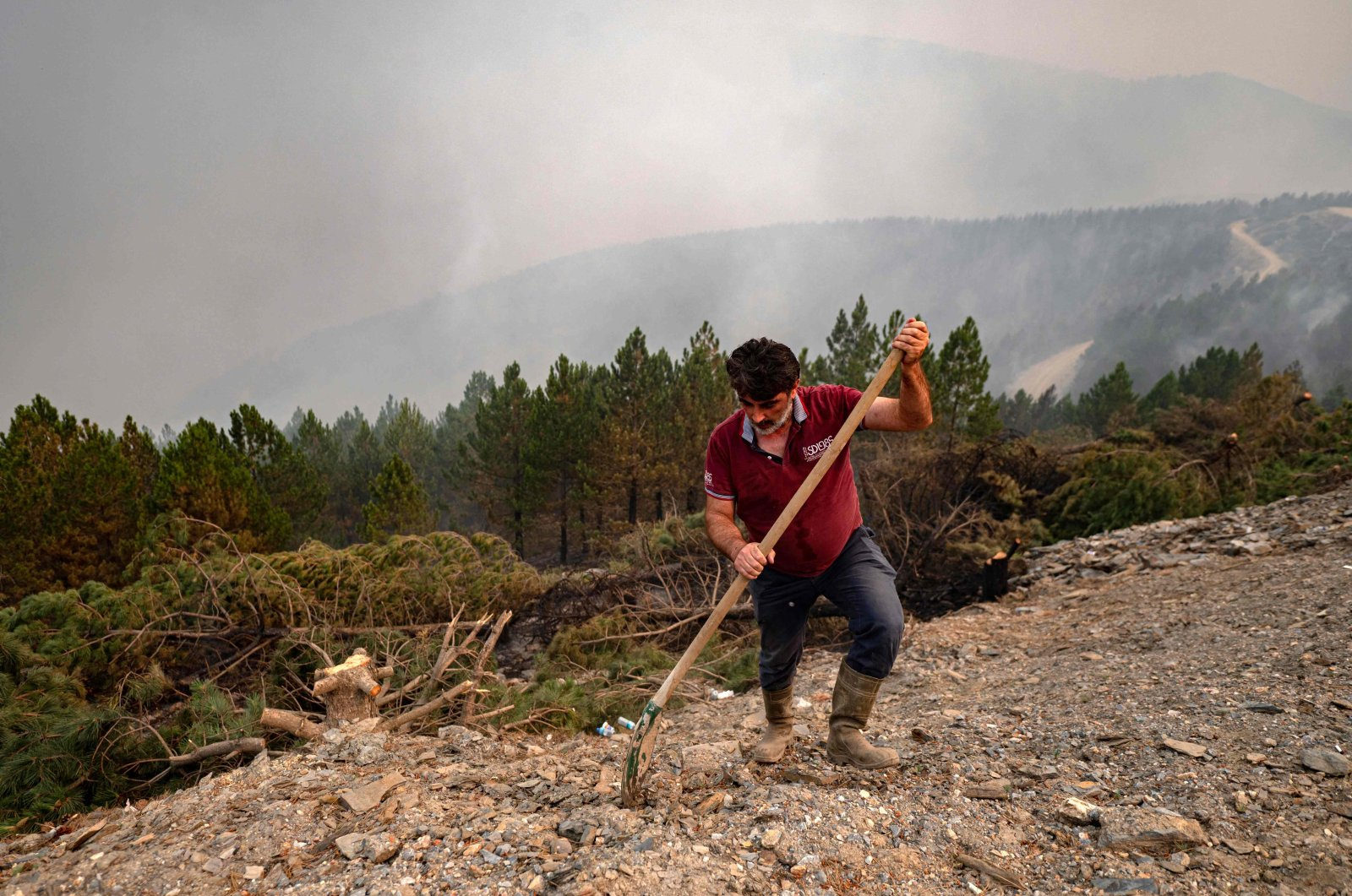 A volunteer from a nearby village uses a shovel to help contain smouldering forest fires in the hills of a recently burnt area near Kavaklıdere, a district of Muğla province, Turkey, Aug. 5, 2021. (AFP Photo)
