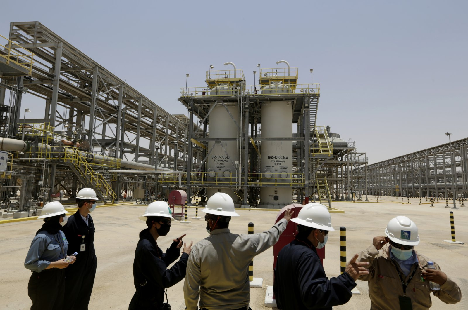 Saudi Aramco engineers and journalists look at the Hawiyah Natural Gas Liquids Recovery Plant, which is designed to process 4.0 billion standard cubic feet per day of sweet gas, a natural gas that does not contain significant amounts of hydrogen sulfide, in Hawiyah, in the Eastern Province of Saudi Arabia, June 28, 2021. (AP Photo)