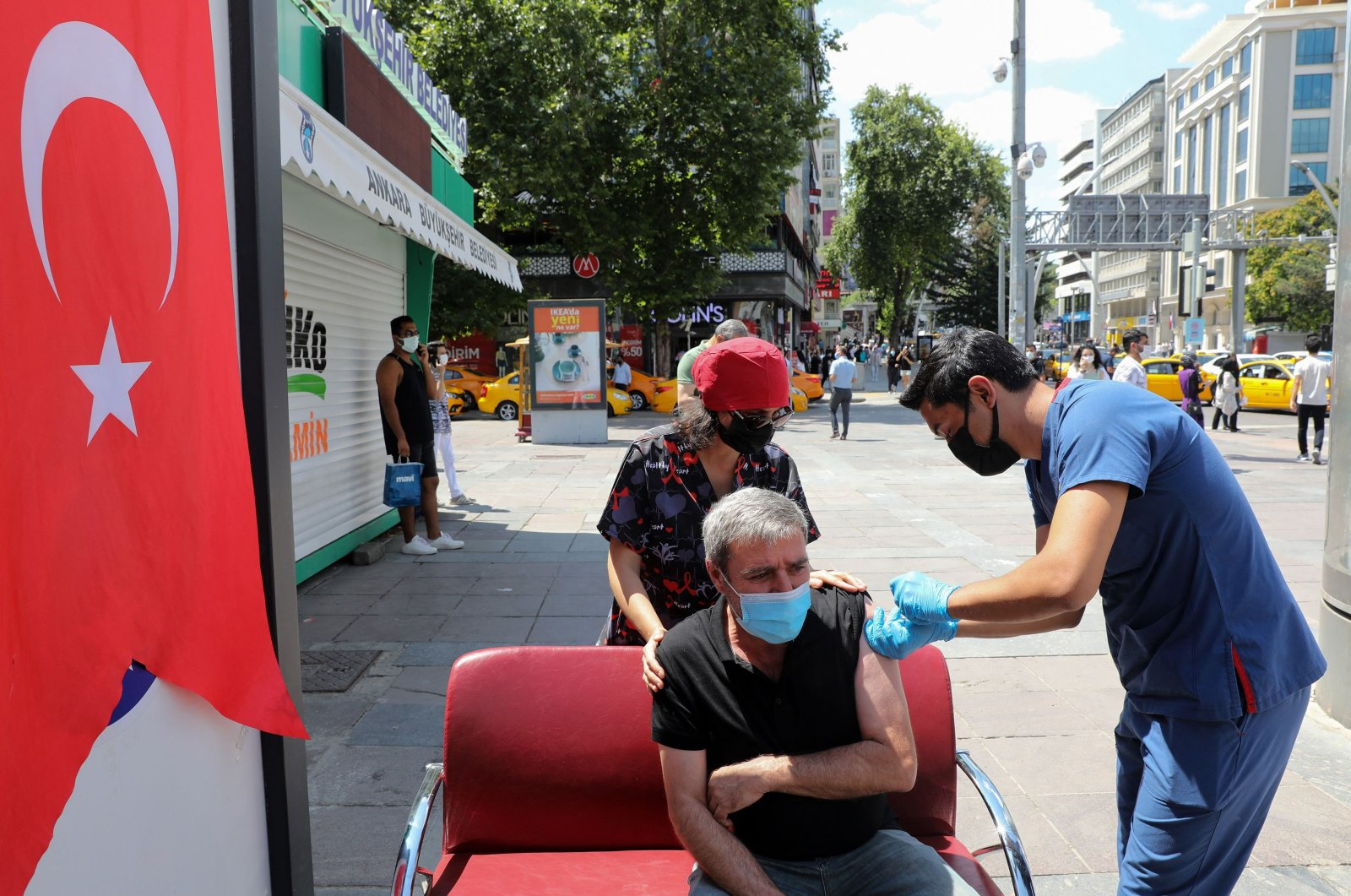 A healthcare worker administers a dose of COVID-19 vaccine to a man at Kizilay Square in Ankara, on July 11, 2021. (AFP Photo)