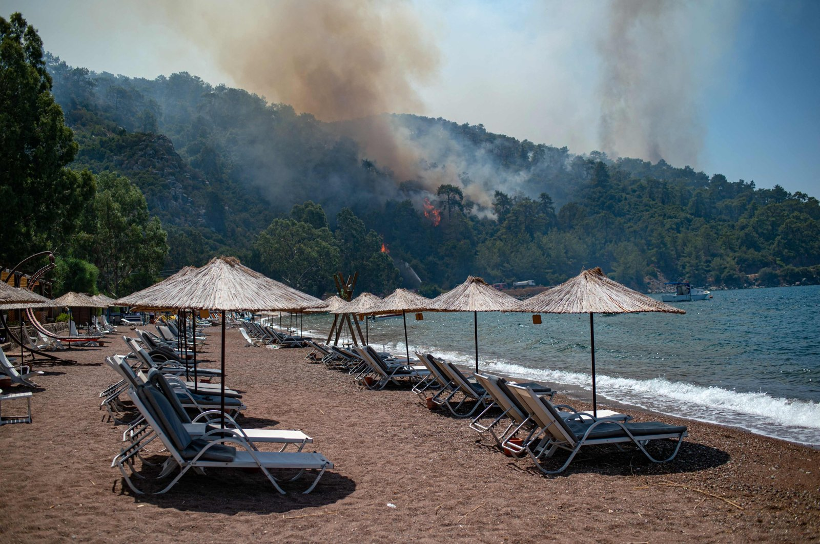 Deck chairs are seen on a beach in front of smoke and flames rising from a forest fire in the Marmaris district of Muğla province, southwestern Turkey, Aug. 3, 2021. (AFP Photo)