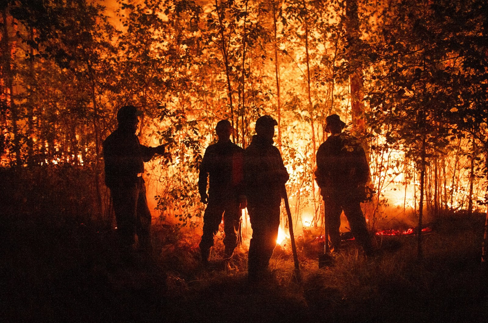 Firefighters work at the scene of a forest fire near Kyuyorelyakh village in Gorny Ulus, west of Yakutsk, in Russia, Aug. 5, 2021. (AP Photo)