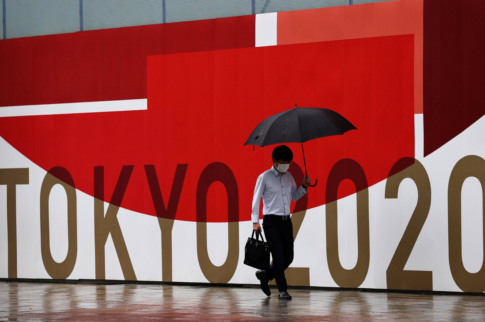 A man in a protective face mask against COVID-19 walks past a Tokyo 2020 sign in Tokyo, Japan, Aug. 8, 2021. (Reuters Photo)