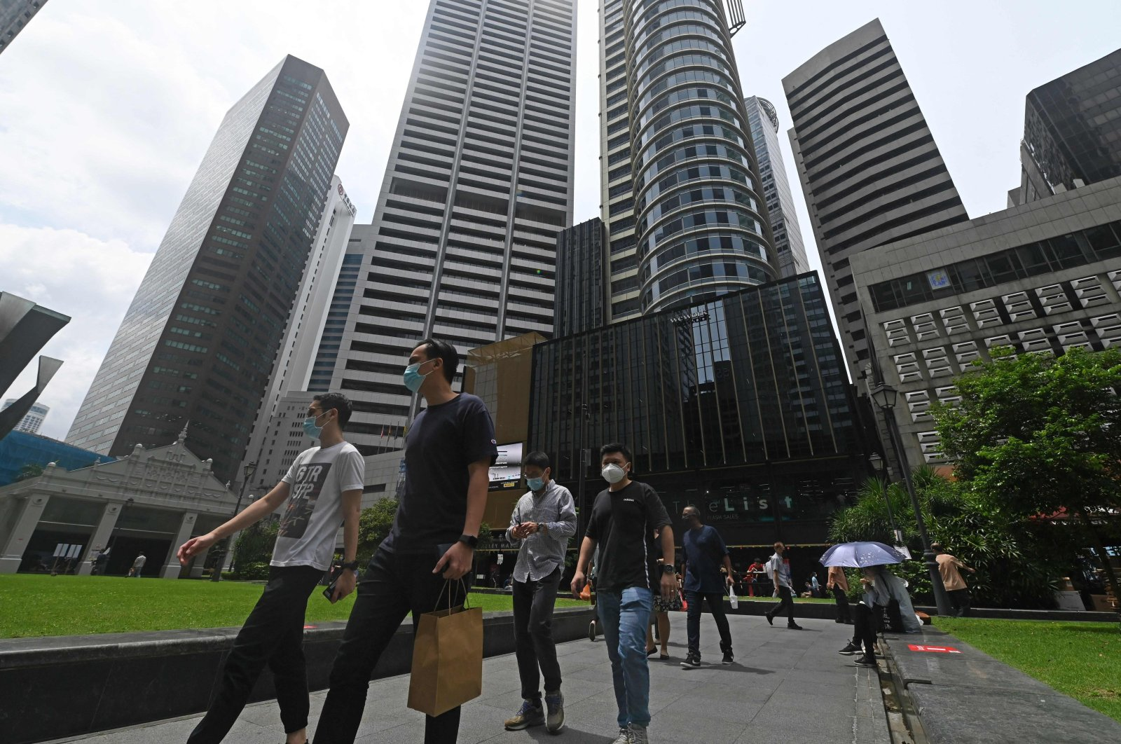 Office workers walk outside during their lunch break at Raffles Place financial business district in Singapore, Aug. 5, 2021. (AFP Photo)