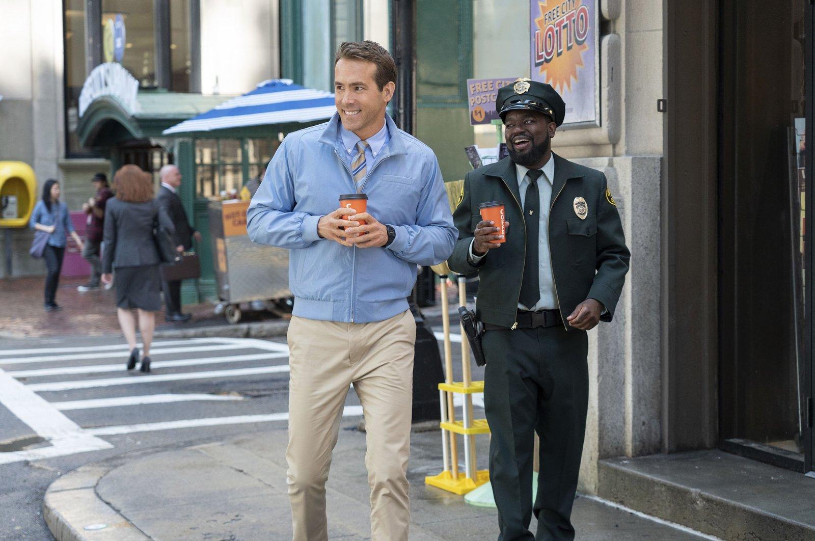 "Ryan Reynolds (L) walks down the street withLil Rel Howeryin ascenefrom the film""Free Guy."" (20th Century Studios via AP)"
