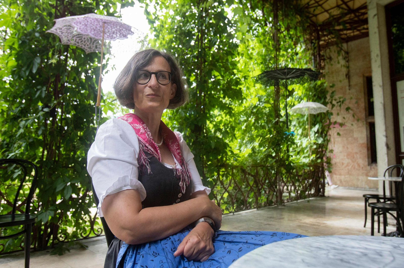 """Thekla Weissengruber, curator of the exhibition """"Dirndl – Tradition goes fashion"""" on display at the Mamorschloessl palace in Bad Ischl, Upper Austria, poses for a photo, June 24, 2021. (AFP Photo)"""