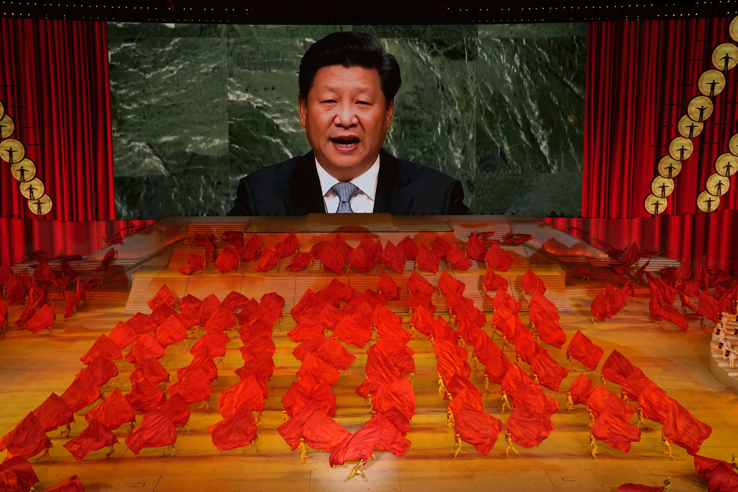 Chinese President Xi Jinping is displayed on a screen as performers dance at a gala ahead of the 100th anniversary of the founding of the Chinese Communist Party in Beijing, China on June 28, 2021. (AP Photo)