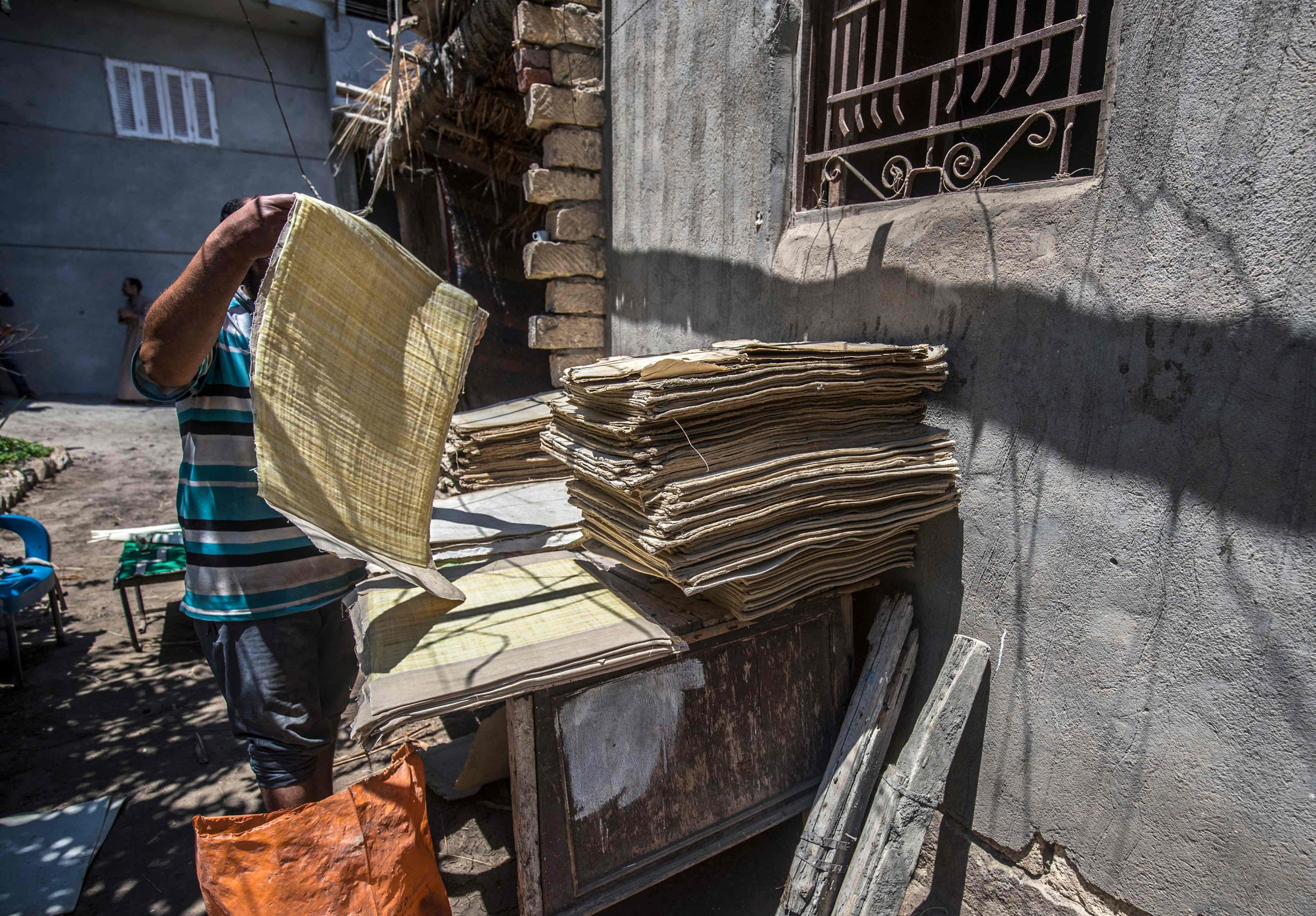 Abdel Mobdi Moussalam, 48, dries papyrus sheets at his workshop in the village of al-Qaramous in Sharqiyah province, in Egypt's northern fertile Nile Delta region, northeast of the capital, July 28, 2021. (AFP Photo)