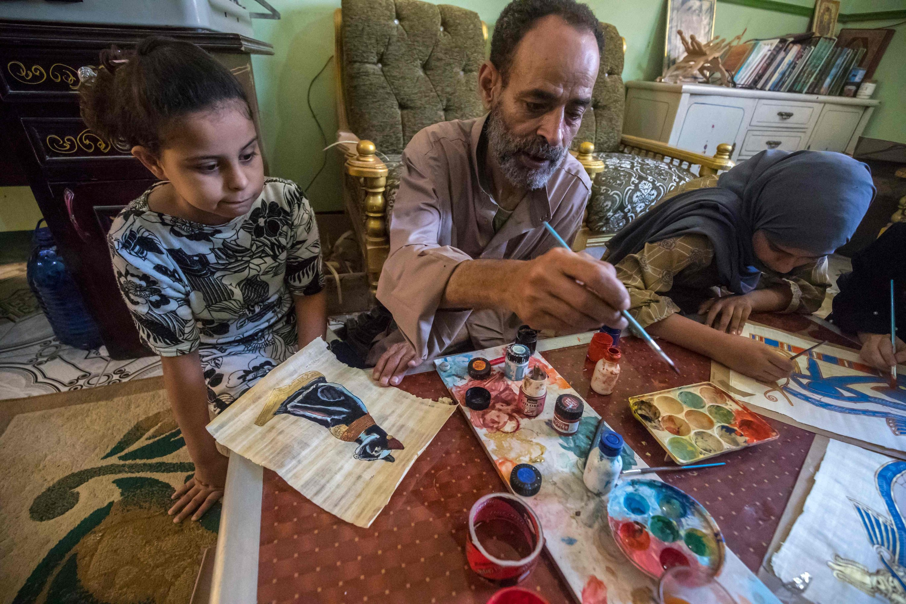Farmer and painter Said Tarakhan, 60, draws on papyrus sheets at home in the village of al-Qaramous in Sharqiyah province, in Egypt's northern fertile Nile Delta region, northeast of the capital, on July 28, 2021. (AFP Photo)