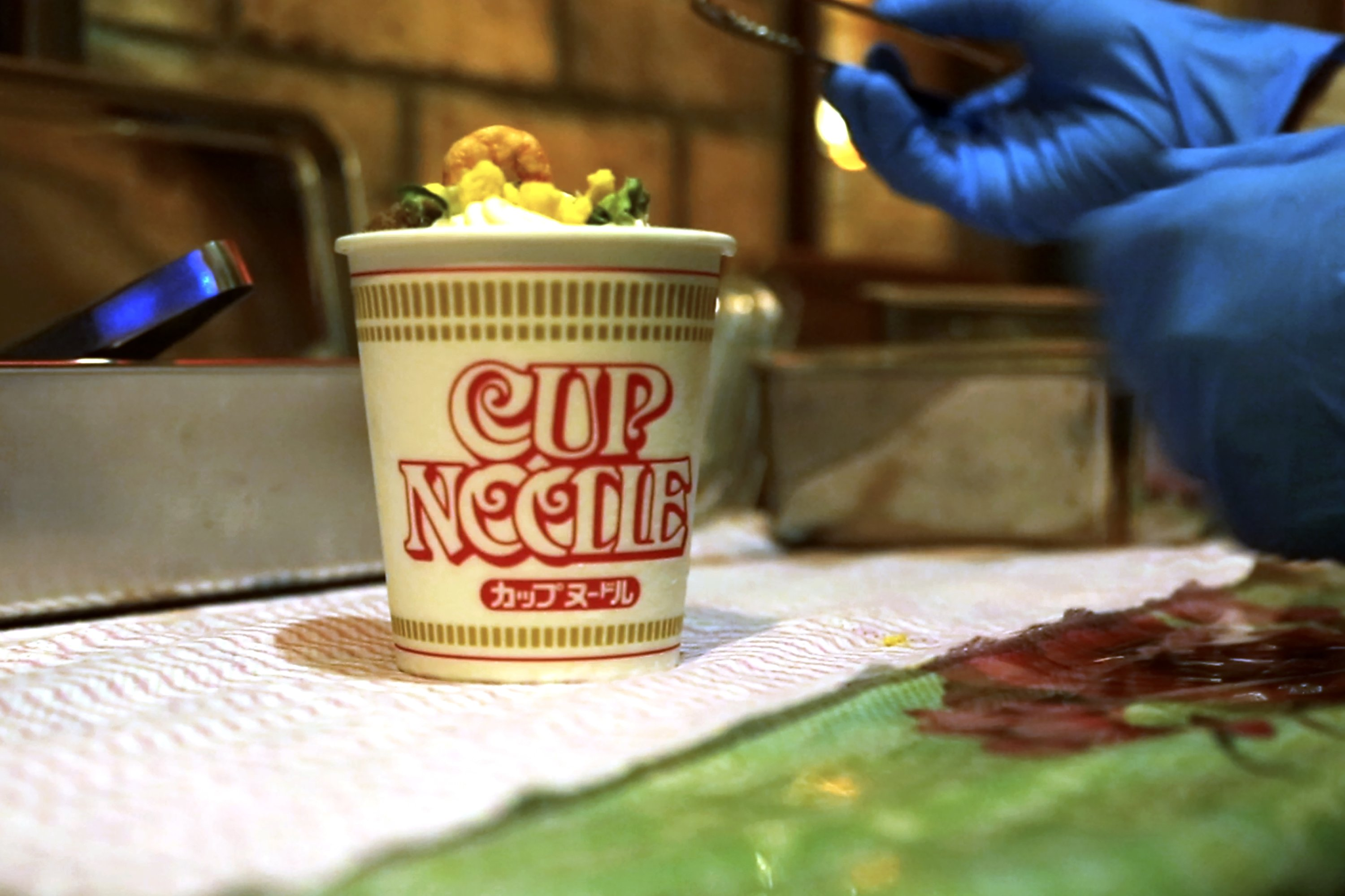 A Cup Noodle ice cream, made with the powdered soup of Cup Noodle and topped with freeze-fried shrimp, onions, egg and meat, is prepared to be eaten at the Cup Noodles Museum in Yokohama, Japan, on Friday, Aug. 6, 2021. (AP Photo)