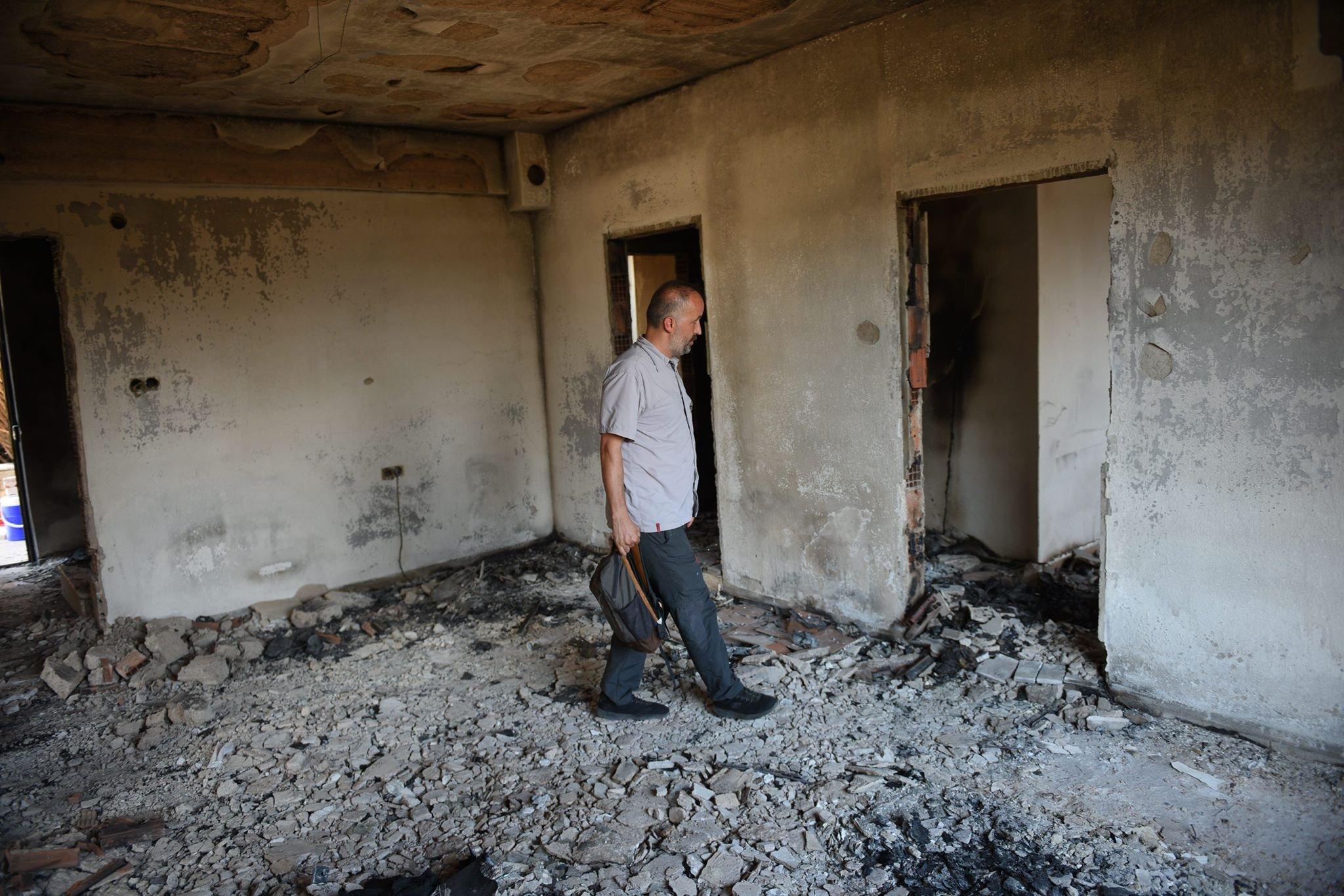 Journalist Zeynel Yaman in a house burned in the fire, in Aşağı Işıklar village, in Antalya, southern Turkey, Aug. 4, 2021. (PHOTO BY MURAT ŞENGÜL)