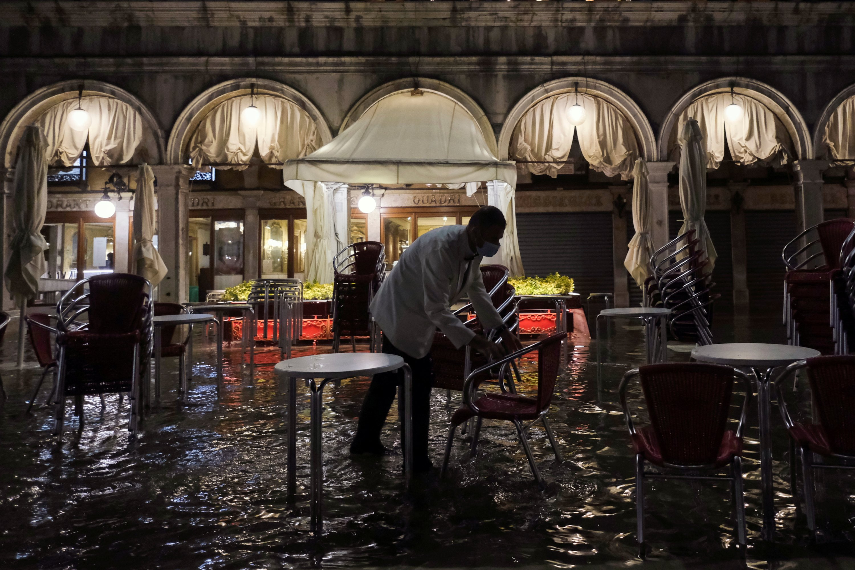 A worker closes a restaurant in a flooded St. Mark's Square after waters rose exceptionally high in Venice, Italy, Aug. 8, 2021. (Reuters Photo)