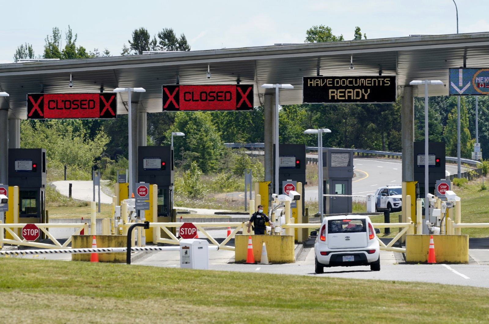 A car approaches one of the few lanes open at the Peace Arch border crossing into the U.S. in Blaine, Wash., June 8, 2021. (AP File Photo)