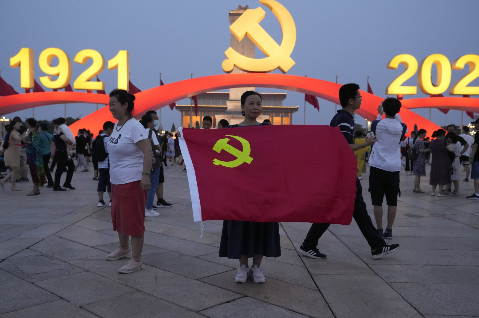 A woman holds up a Communist Party flag as she poses for photos near decorations to mark the 100th anniversary of the founding of the ruling Chinese Communist Party on Tiananmen Square in Beijing, China, on July 15, 2021. (AP Photo)