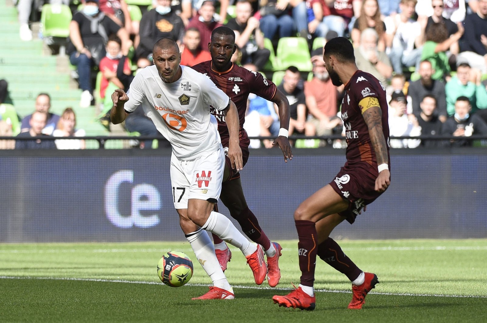 Lille's Turkish forward Burak Yılmaz (L) fights for the ball with Metz's defender Boubakar Kouyate (C) and Dylan Bronn (R) during the French L1 match at Stade Saint-Symphorien in Longeville-les-Metz, northern France, Aug. 8, 2021. (AFP Photo)