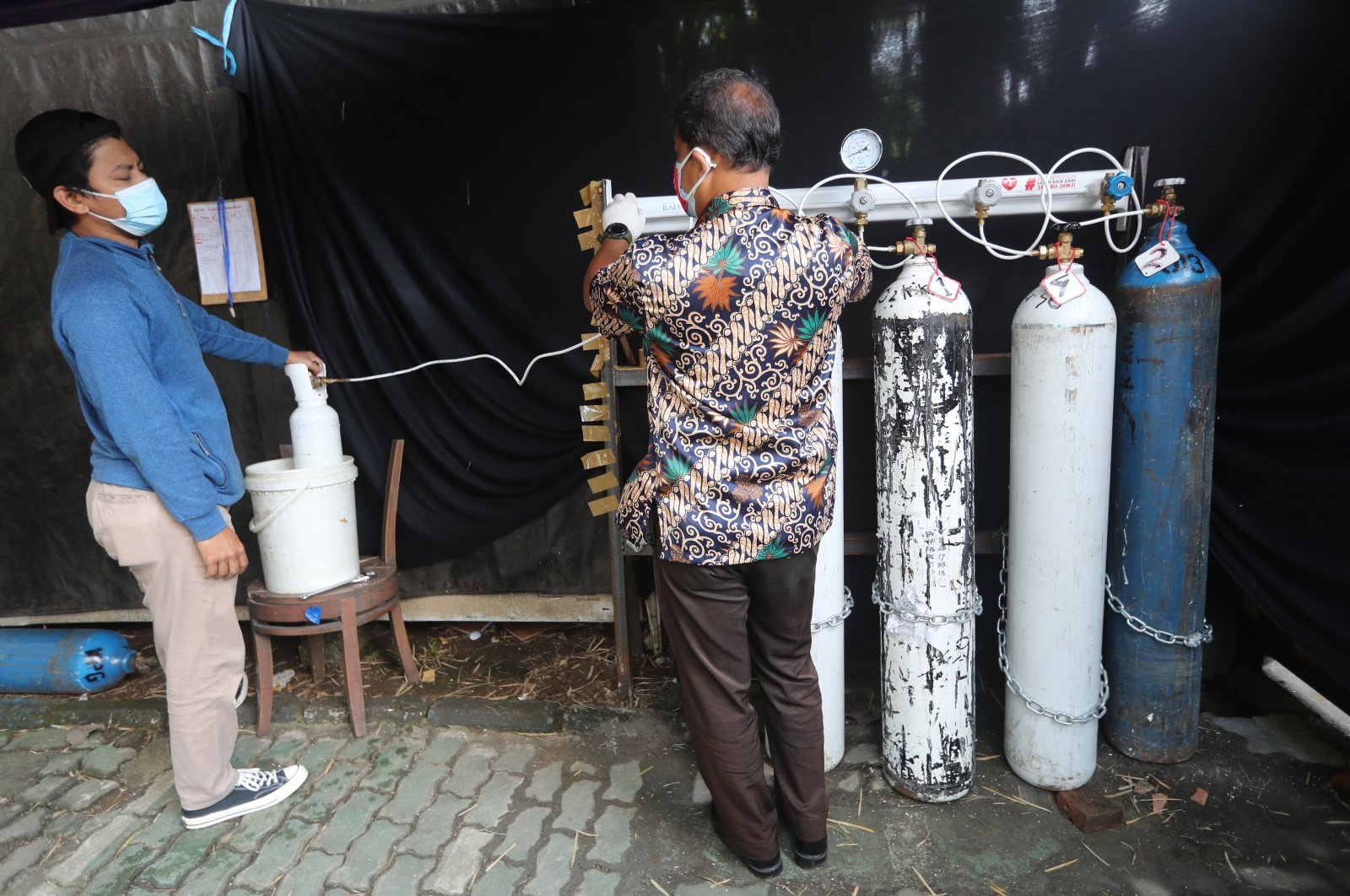 Two Indonesian volunteers refill oxygen tubes at a free oxygen refill station amid a rising number of COVID-19 cases, at Graha Pena Building in Bogor, Indonesia, 06 August 2021. (EPA Photo)