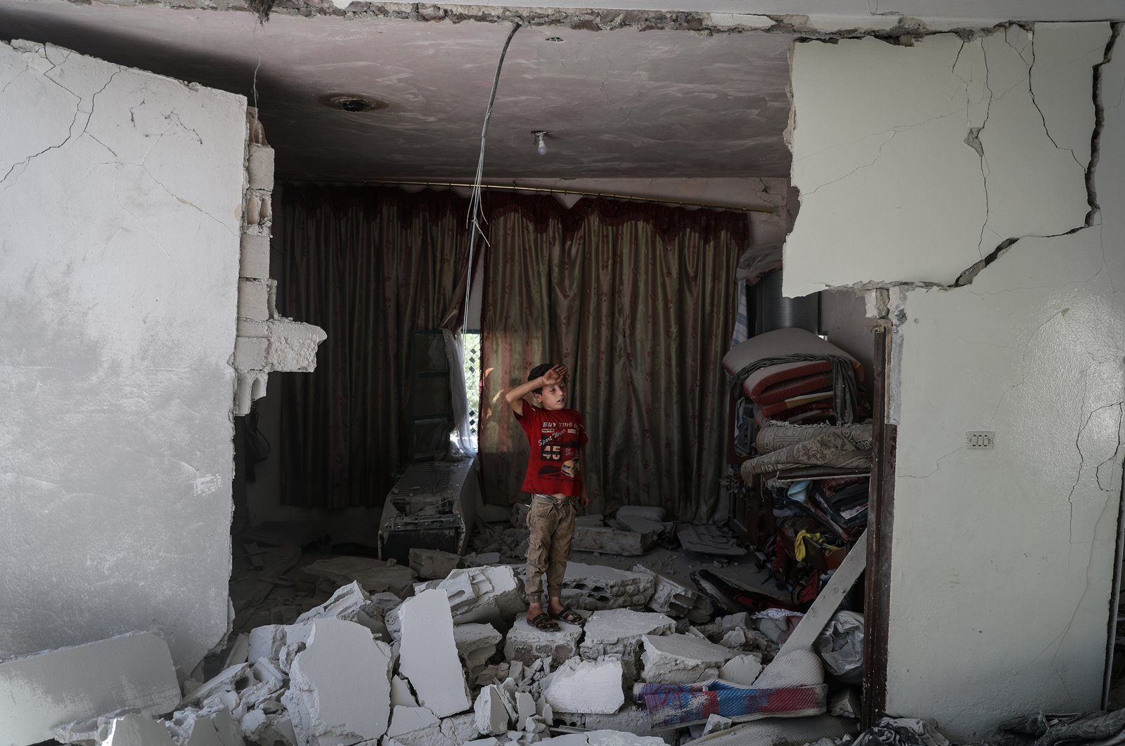 A child inspects a damaged building targeted by a missile in the village of Iblin, Syria, July 15, 2021. (Getty Images)