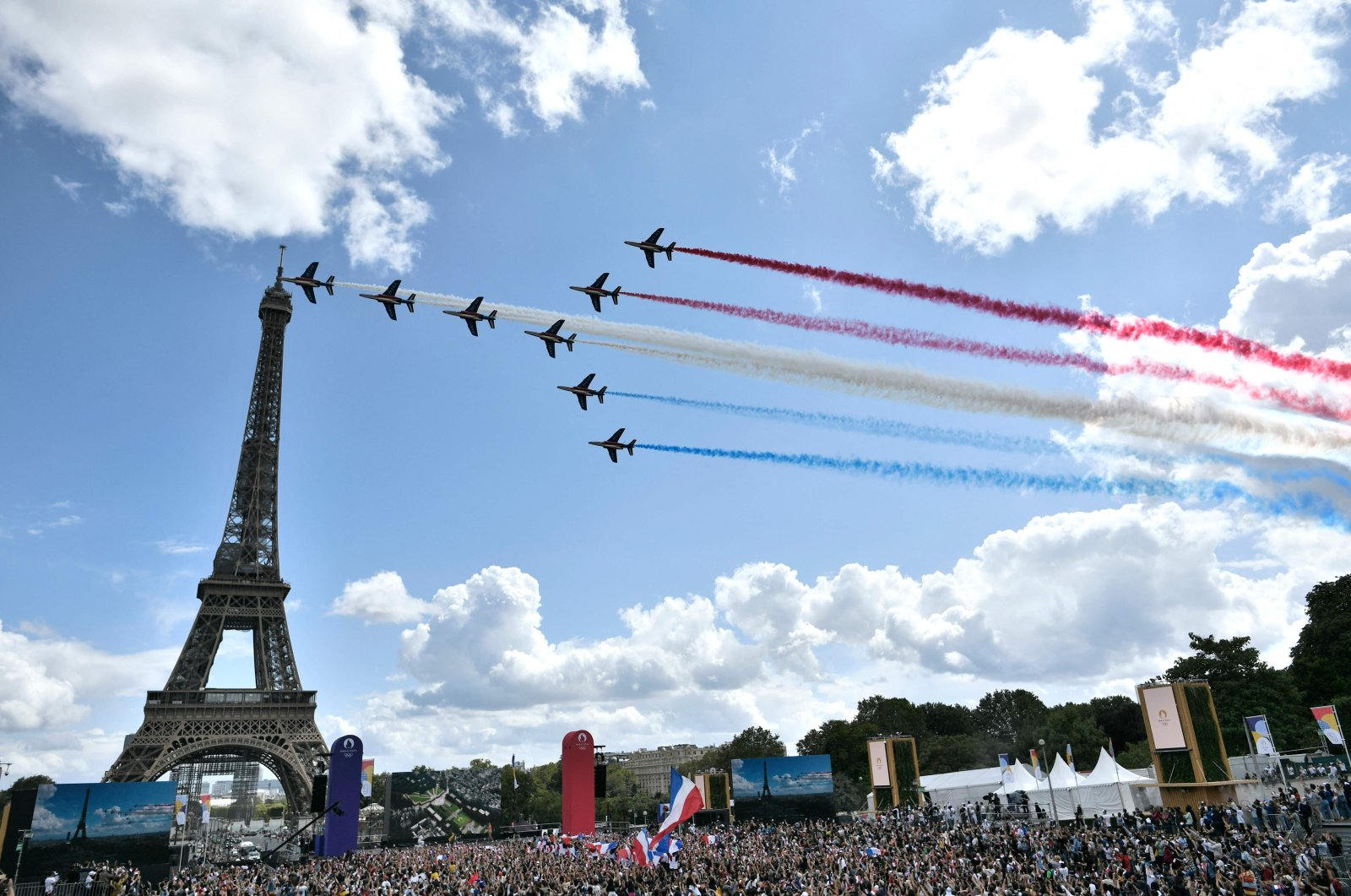"""French aerial patrol """"Patrouille de France"""" fly over the fan village of The Trocadero set in front of The Eiffel Tower upon the transmission of the closing ceremony of the Tokyo 2020 Olympic Games, in Paris, Aug. 8, 2021. (AFP Photo)"""