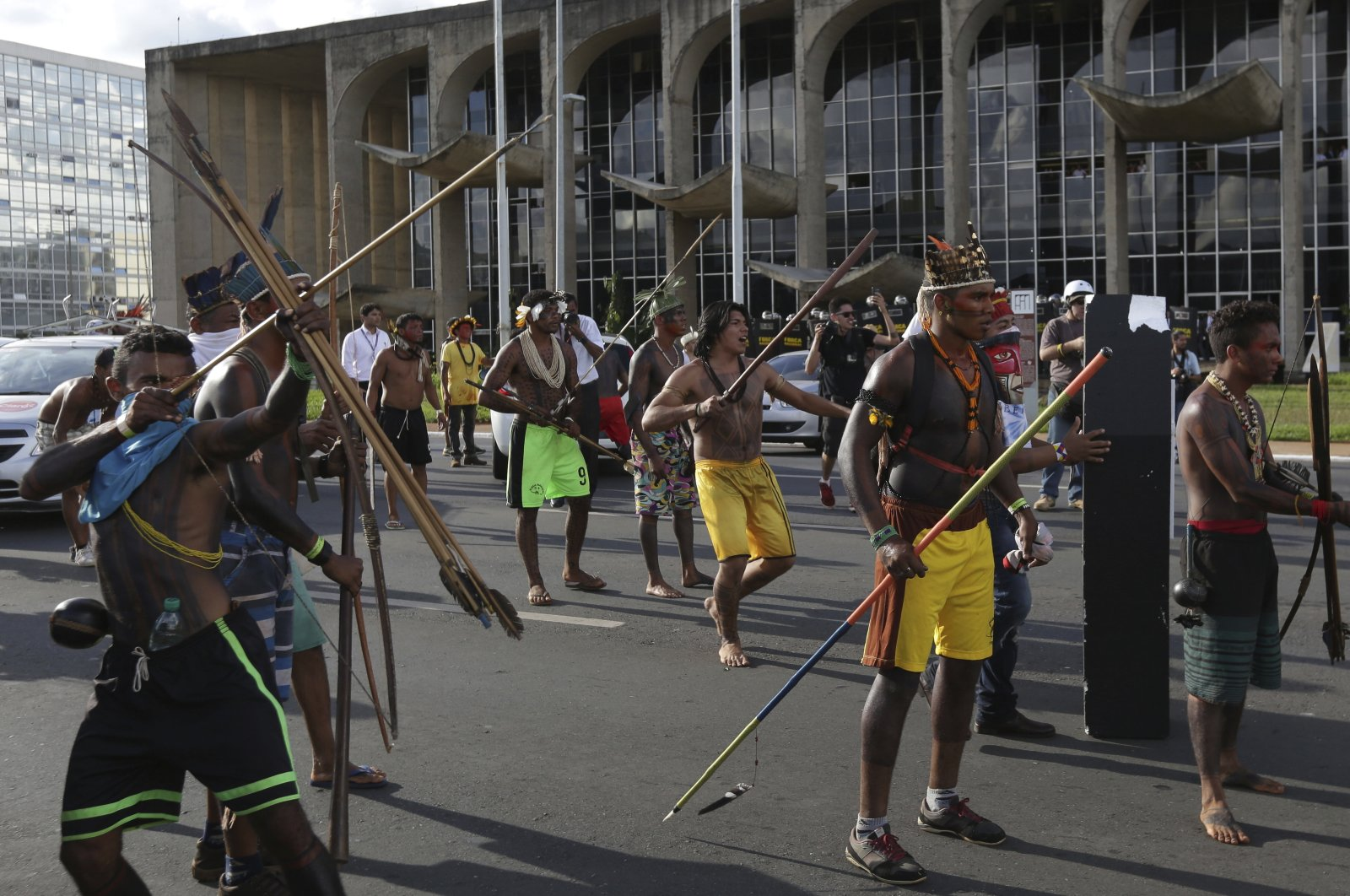 An Indigenous man aims his arrow at police outside the National Congress during a protest for the demarcation of Indigenous lands in Brasilia, Brazil, April 25, 2017. (AP Photo)