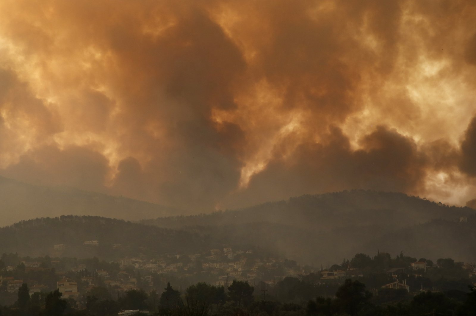 Smoke spreads over Parnitha mountain during a wildfire in the village of Ippokratios Politia, Greece, about 35 kilometres (21 miles), north of Athens, Greece, Aug. 6, 2021. (AP Photo)