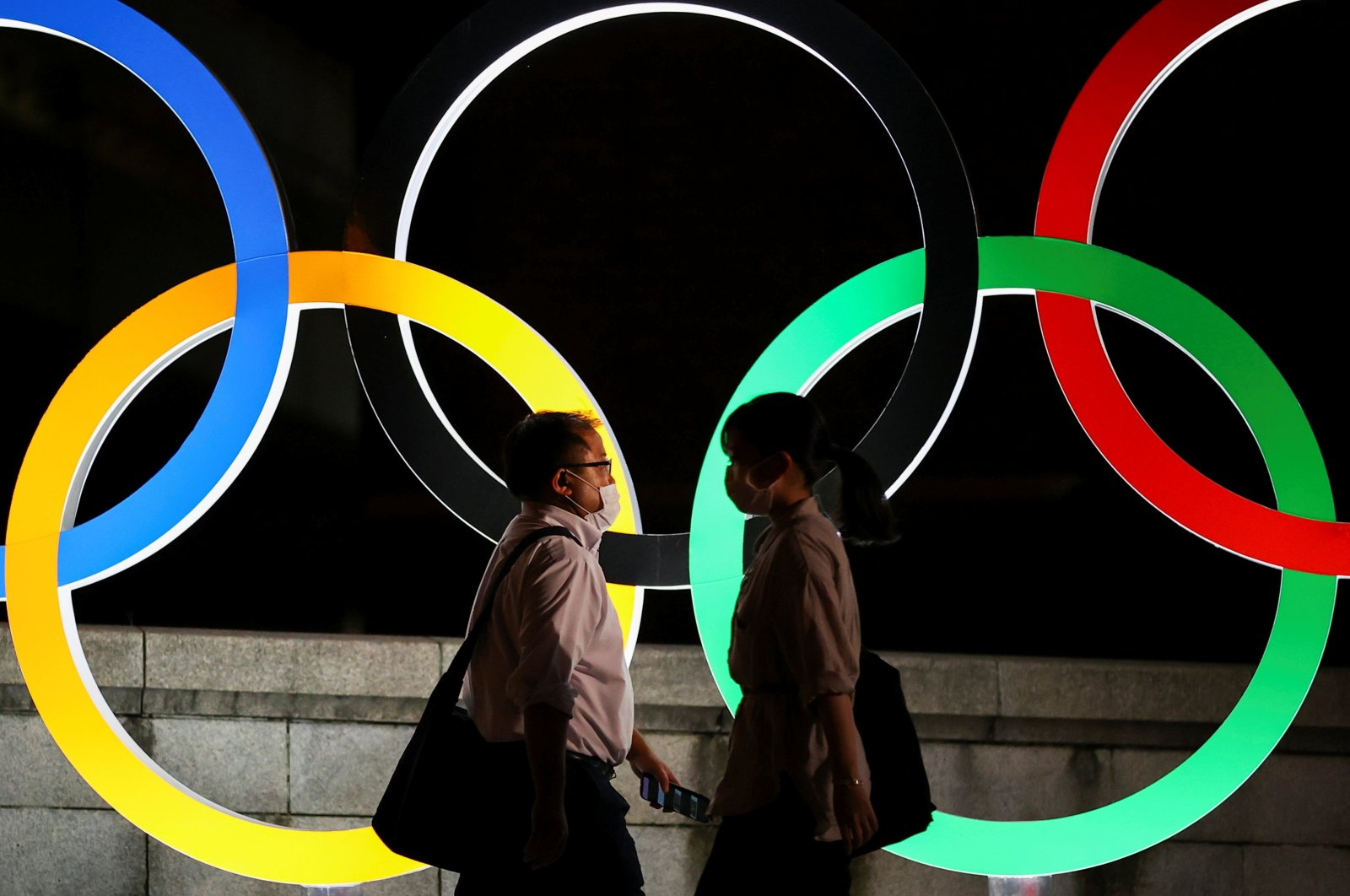 Passersby wearing protective face masks walk past an illuminated Olympic Rings monument during the Tokyo 2020 Olympic Games, Tokyo, Japan, Aug. 5, 2021. (Reuters Photo)