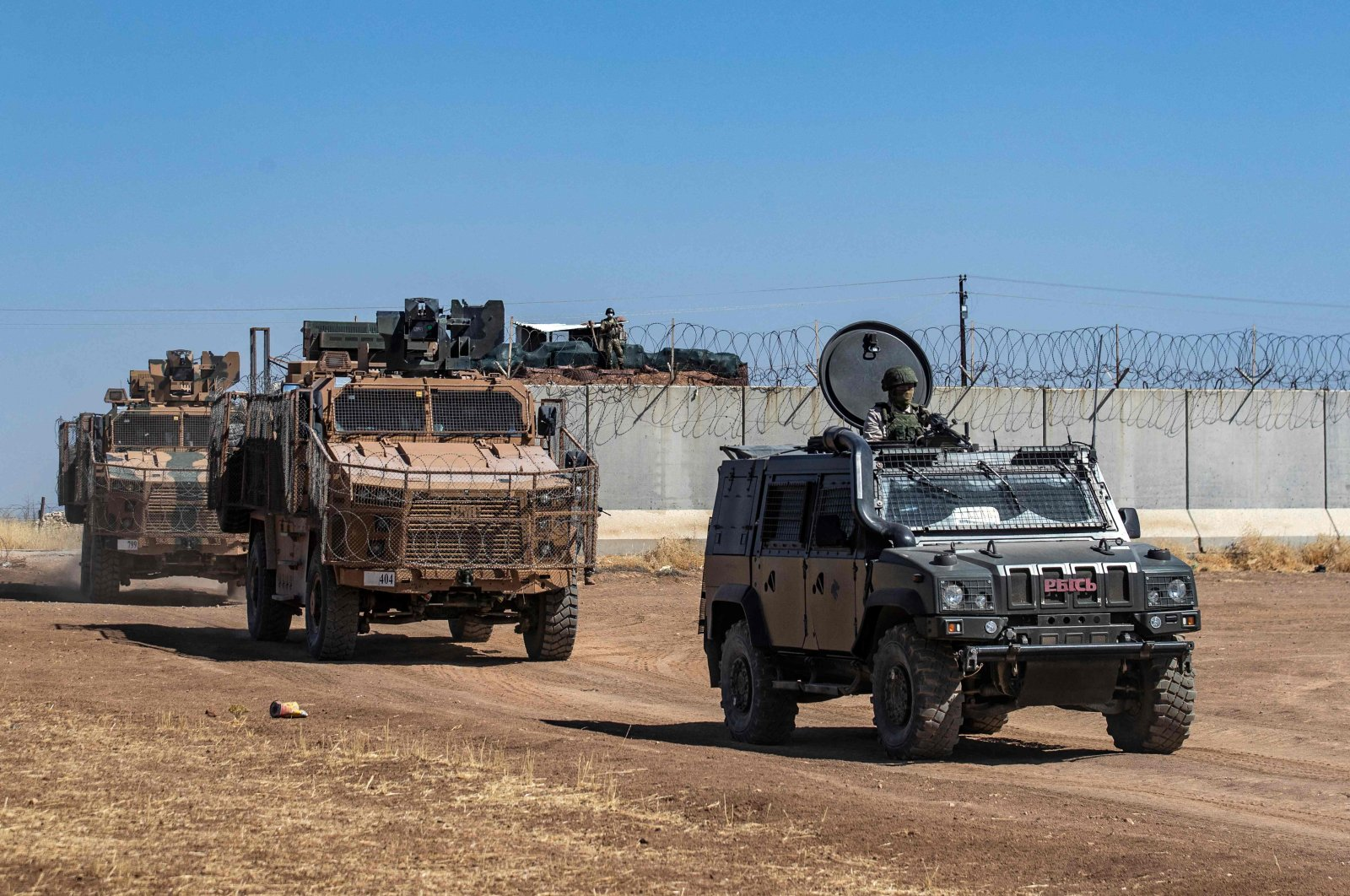 A joint Russian (R) and Turkish (L) convoy of military vehicles start a patrol from the border with Turkey, in the countryside of the town of Derbassiye in northeastern Hasakeh province, Syria, on July 14, 2021. (AFP Photo)
