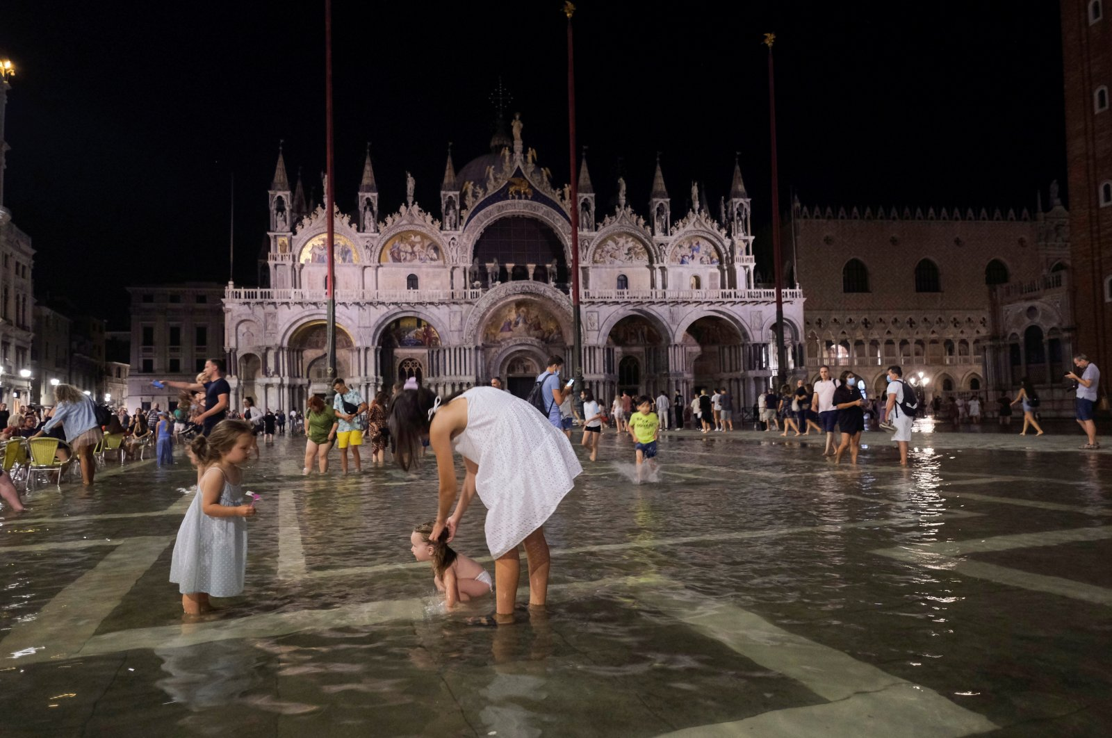 People walk in a flooded St. Mark's Square after waters rose exceptionally high in Venice, Italy, Aug. 8, 2021. (Reuters Photo)