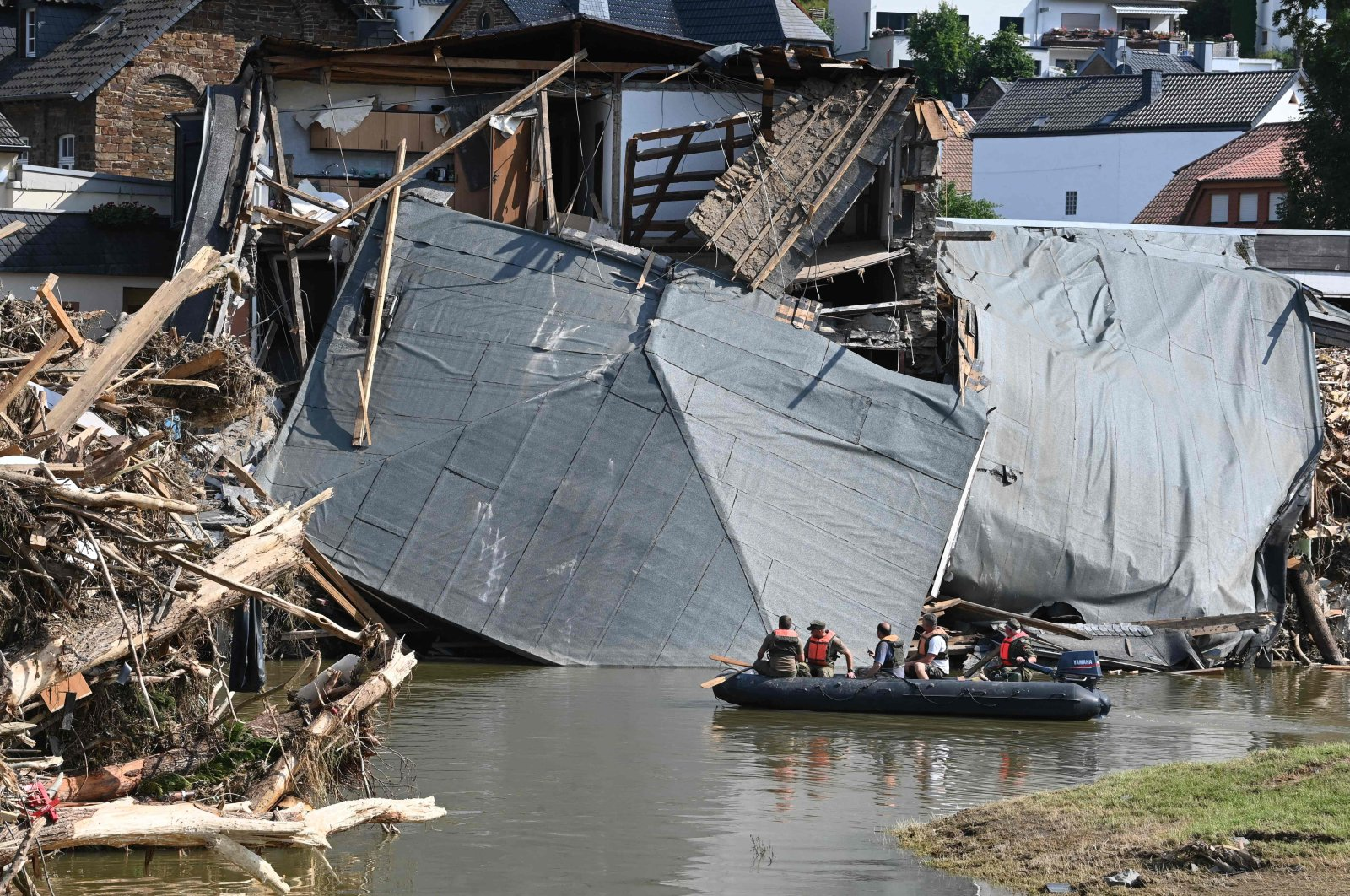 Military personnel floats on a boat on the Ahr river as the roof of a damaged house hangs on the water in Rech, Rhineland-Palatinate, after devastating floods hit the region, western Germany, July 21, 2021. (AFP Photo)
