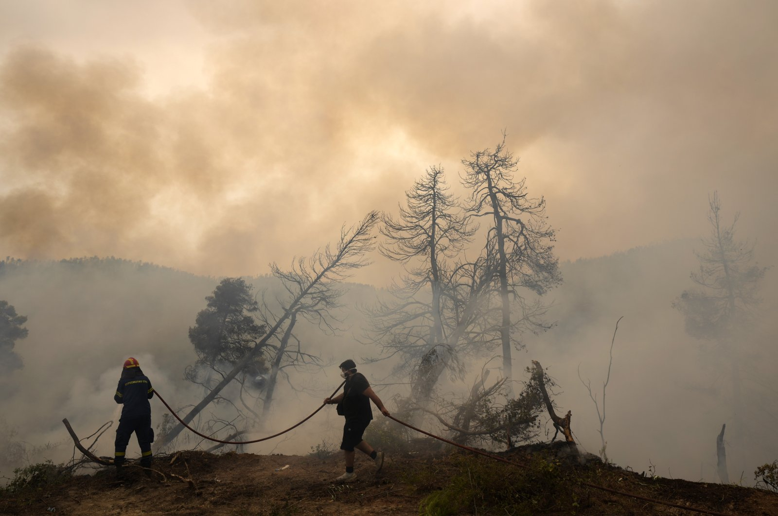 A firefighter tries to extinguish the flames as a local resident holds a water hose during a wildfire at Ellinika village on Evia island, about 176 kilometers (110 miles) north of Athens, Greece, Aug. 9, 2021. (AP Photo)