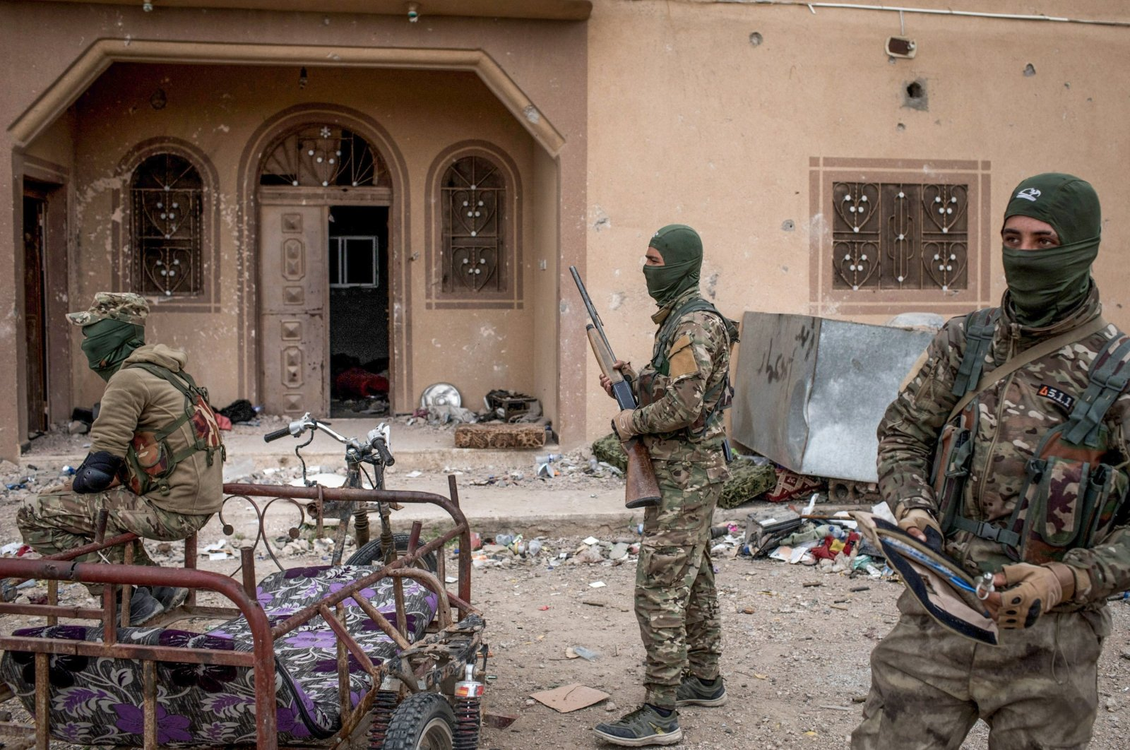 YPG/PKK terrorists are seen in front of a building in Baghouz, Syria, on March 24, 2019. (Photo by Chris McGrath/Getty Images)