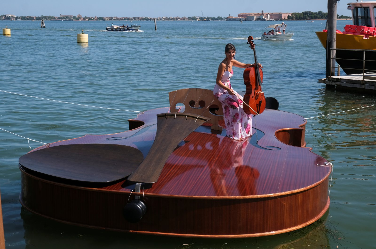 A musician plays cello on board a boat in the shape of a violin, titled 'Violin of Noah', that was built during the pandemic by artist Livio De Marchi in collaboration with Consorzio Venezia Sviluppo and is dedicated to people who have died from coronavirus, during a test-ride, in Venice, Italy, Aug. 6, 2021. (Reuters Photo)