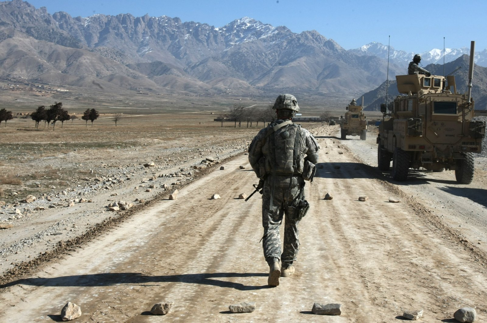 A U.S. soldier from a Provincial Reconstruction Team (PRT) walks along a road under construction near Bagram, about 60 kilometers (about 37 miles) from Kabul, Afghanistan, Jan. 11, 2010. (AFP Photo)