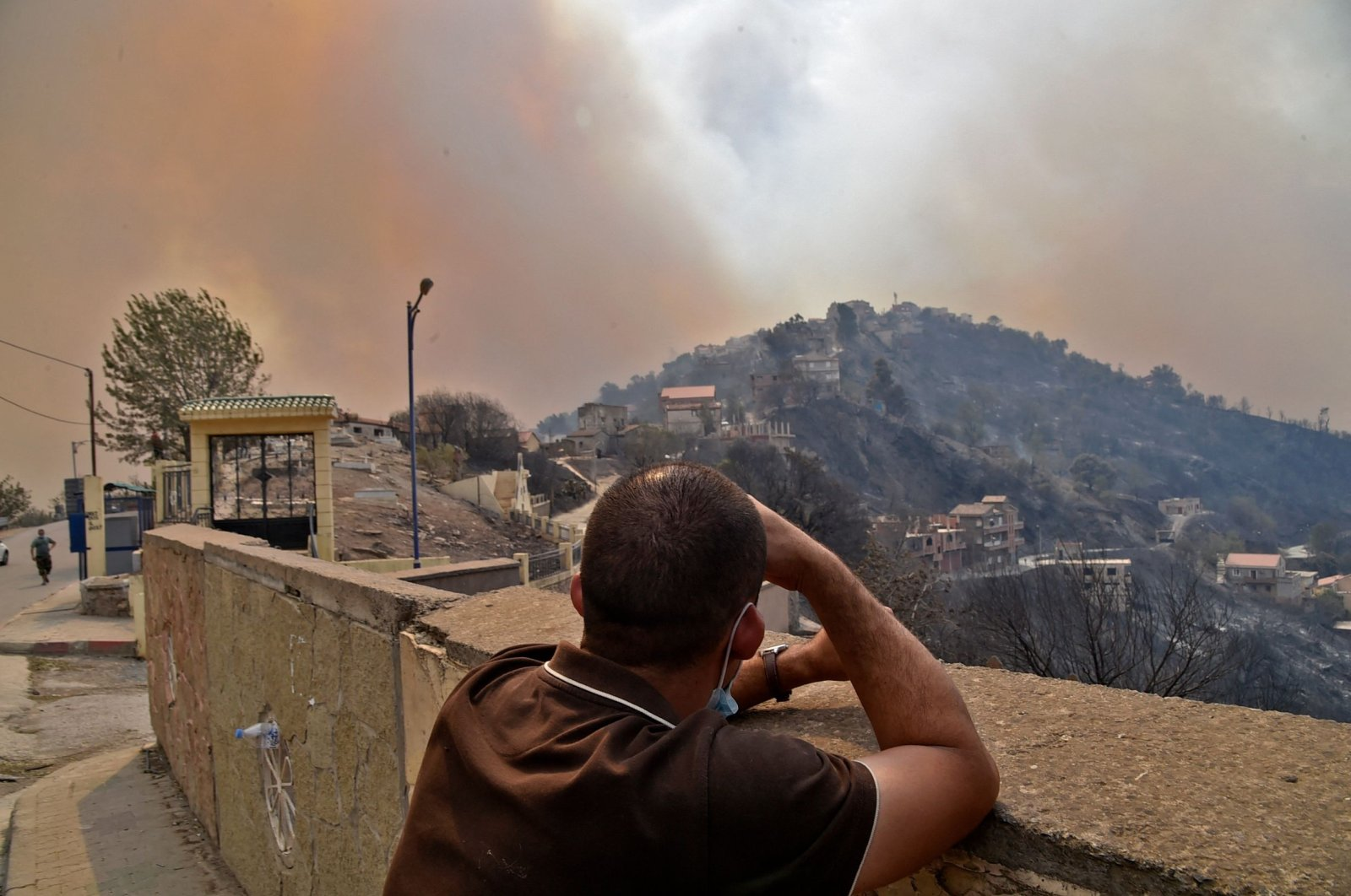 A man looks on as smoke rises from a wildfire in the forested hills of the Kabylie region, east of the capital Algiers, Algeria, on Aug. 10, 2021. (AFP Photo)