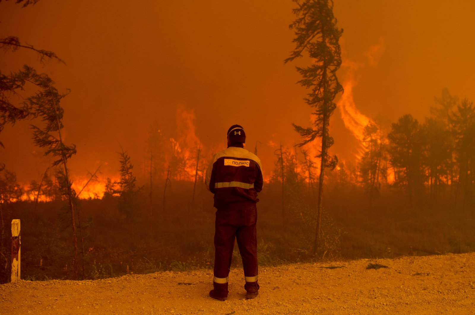 A firefighter stands at the scene of forest fire near Kyuyorelyakh village at Gorny Ulus area west of Yakutsk, in Russia, Saturday, Aug. 7, 2021. (AP Photo)