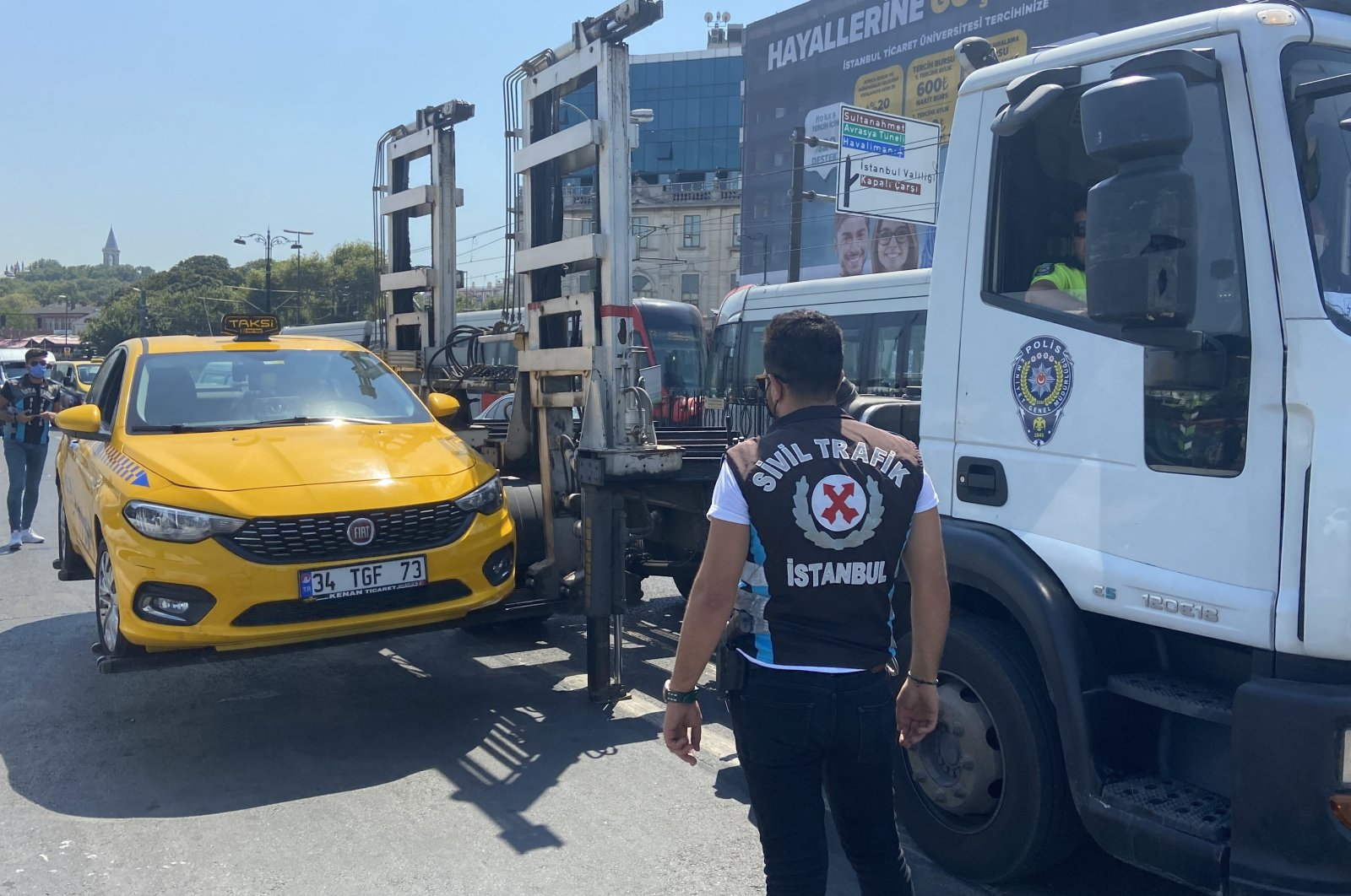 Police officers impound a taxi whose driver violated rules, in Eminönü quarter, in Istanbul, Turkey, Aug. 10, 2021. (IHA PHOTO)