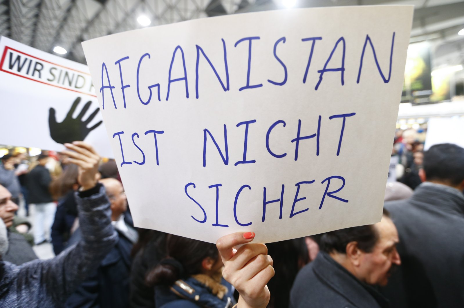 """Protesters hold a placard reading """"Afghanistan is not secure"""" during a demonstration against the deportation of Afghan asylum seekers from Germany back to Afghanistan, at Frankfurt Airport, Germany, Dec. 14, 2016. (Reuters Photo)"""