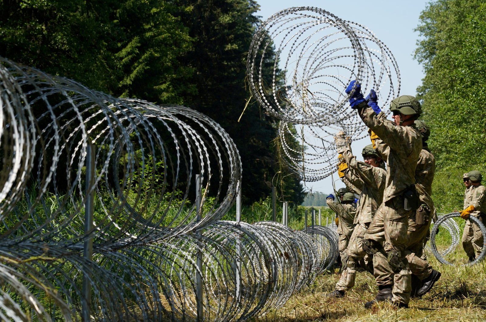 Lithuanian army soldiers install razor wire on the border with Belarus in Druskininkai, Lithuania July 9, 2021. (Reuters Photo)
