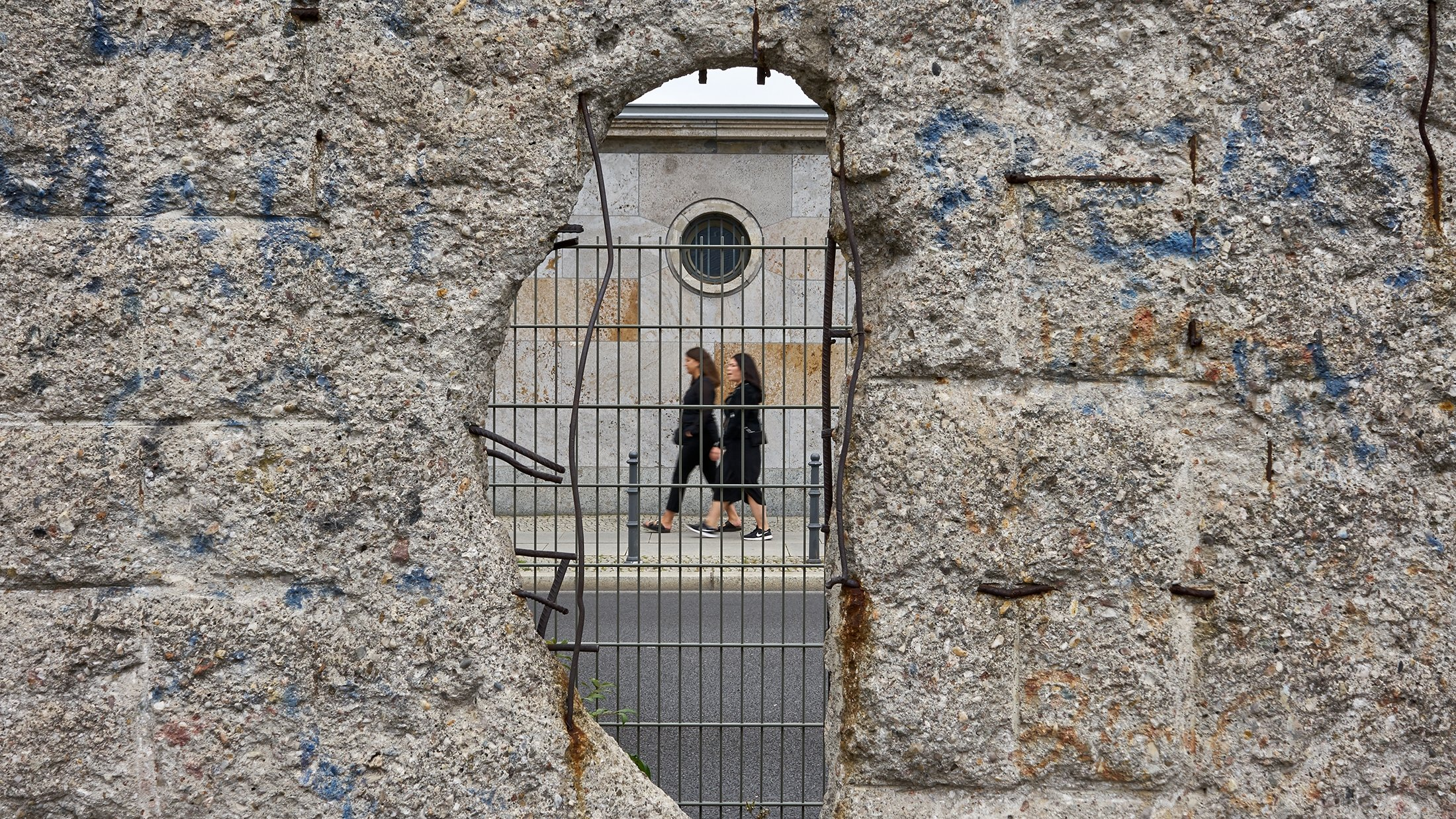 Two blurred female figures walk along a sidewalk as seen through a hole in the landmark location of the Berlin Wall in Berlin, Germany, Aug. 2019. (Shutterstock Photo)