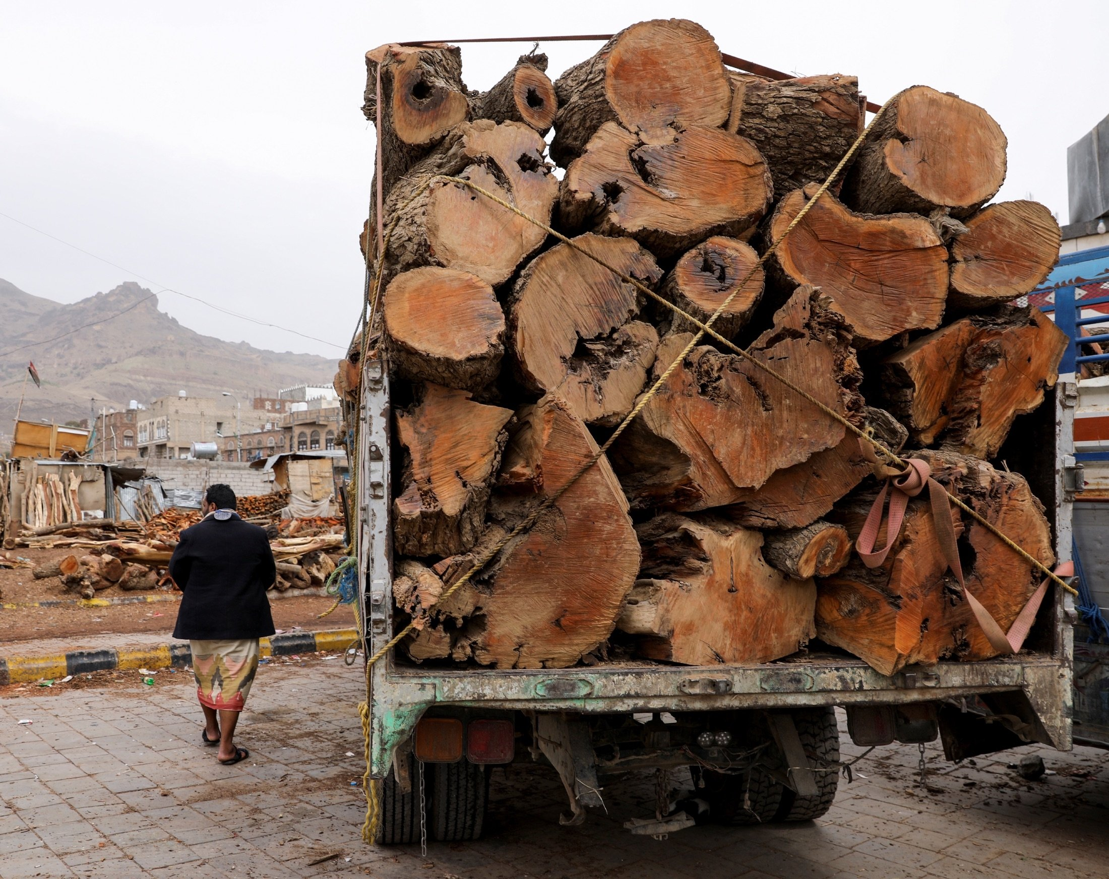 A man walks by a truck loaded with logs at a firewood market in Sanaa, Yemen, July 17, 2021. (Reuters Photo)