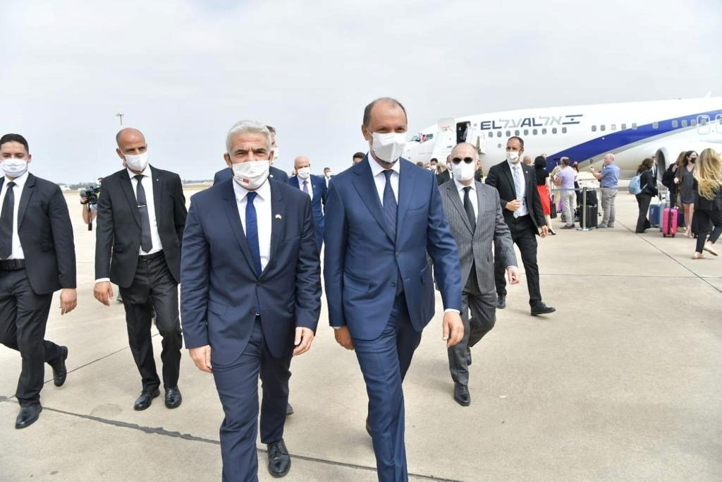 Israeli Foreign Minister Yair Lapid walks with Minister Delegate to the Moroccan Foreign Ministry Mohcine Jazouli, upon his arrival at the airport in Rabat, Morocco August 11, 2021. (Israel Ministry of Foreign Affairs via Reuters)