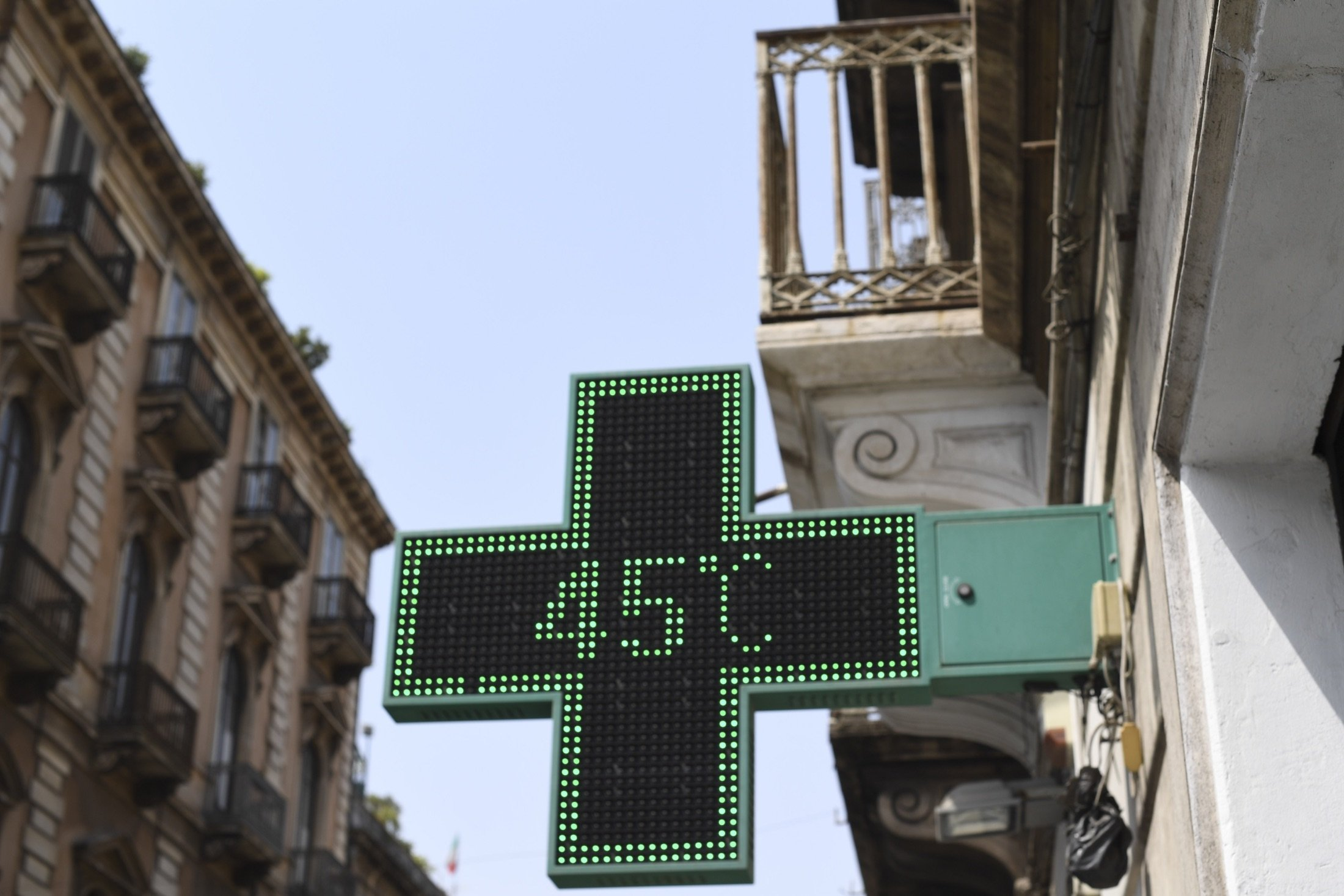 A pharmacy thermometer reports the temperature of 45 degrees Celsius in a street of Catania, Sicily,  Southern Italy, Aug. 11, 2021. (AP Photo)