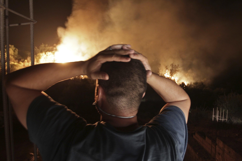 A man looks at a forest fire near the village of Larbaa Nath Irathen, near Tizi Ouzou, in the mountainous Kabyle region, 100 kilometers (60 miles) east of Algeria's capital of Algiers, Aug.11, 2021. (AP Photo)