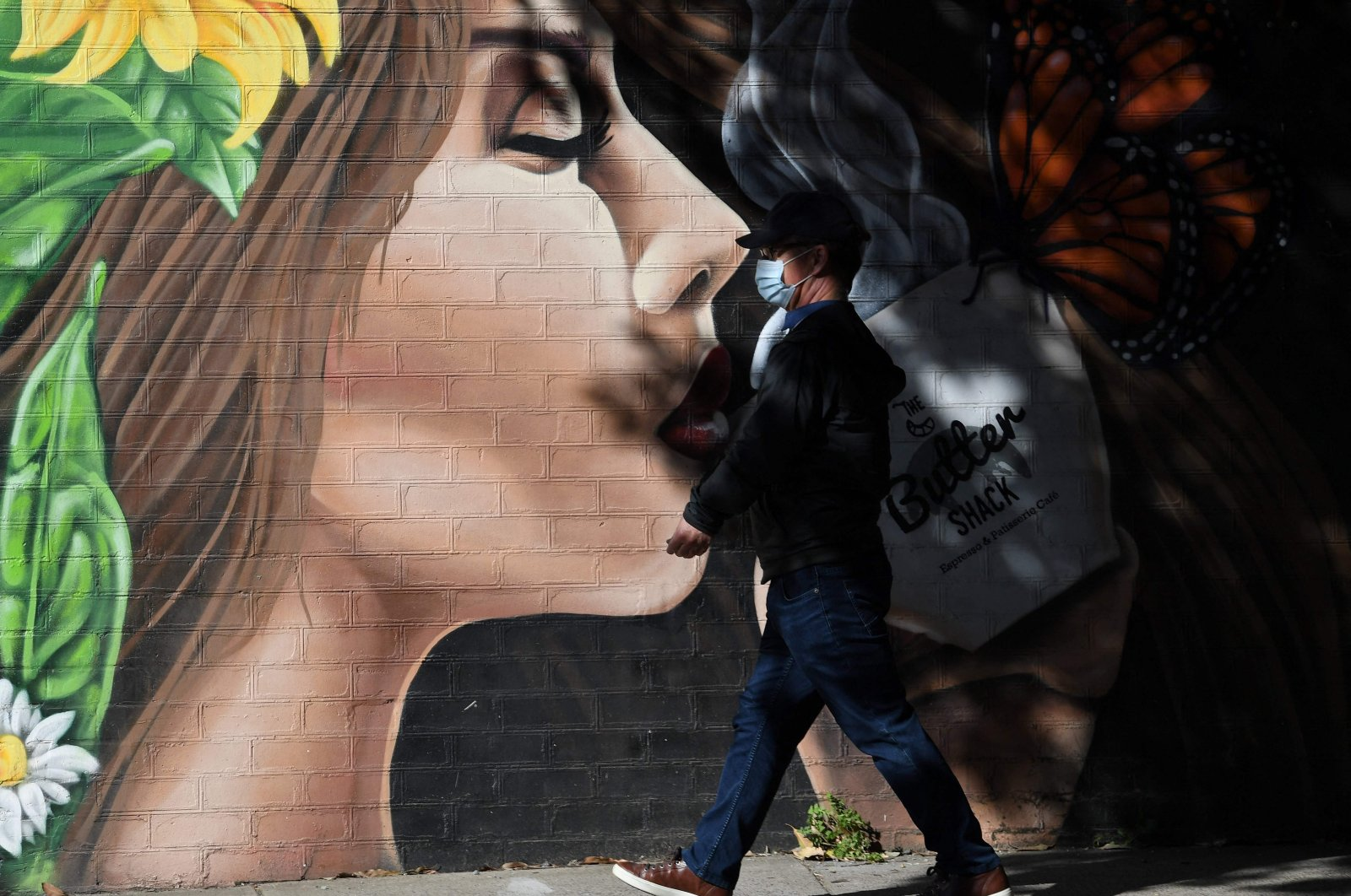 A man wearing a face mask walks in front of a cafe in a suburb of Sydney, as the city's more than 5 million people are enduring their seventh week under stay-at-home orders, Sydney, Australia, Aug. 11, 2021. (AFP Photo)