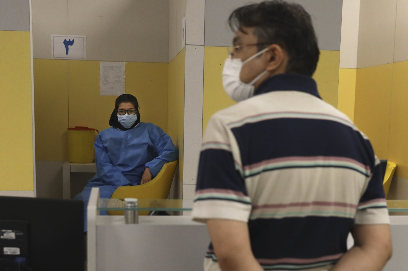 A health worker, left, waits to vaccinate people against COVID-19 as a man waits his turn at a vaccination center in Iran Mall in Tehran, Iran, Aug. 9, 2021. (AP Photo)